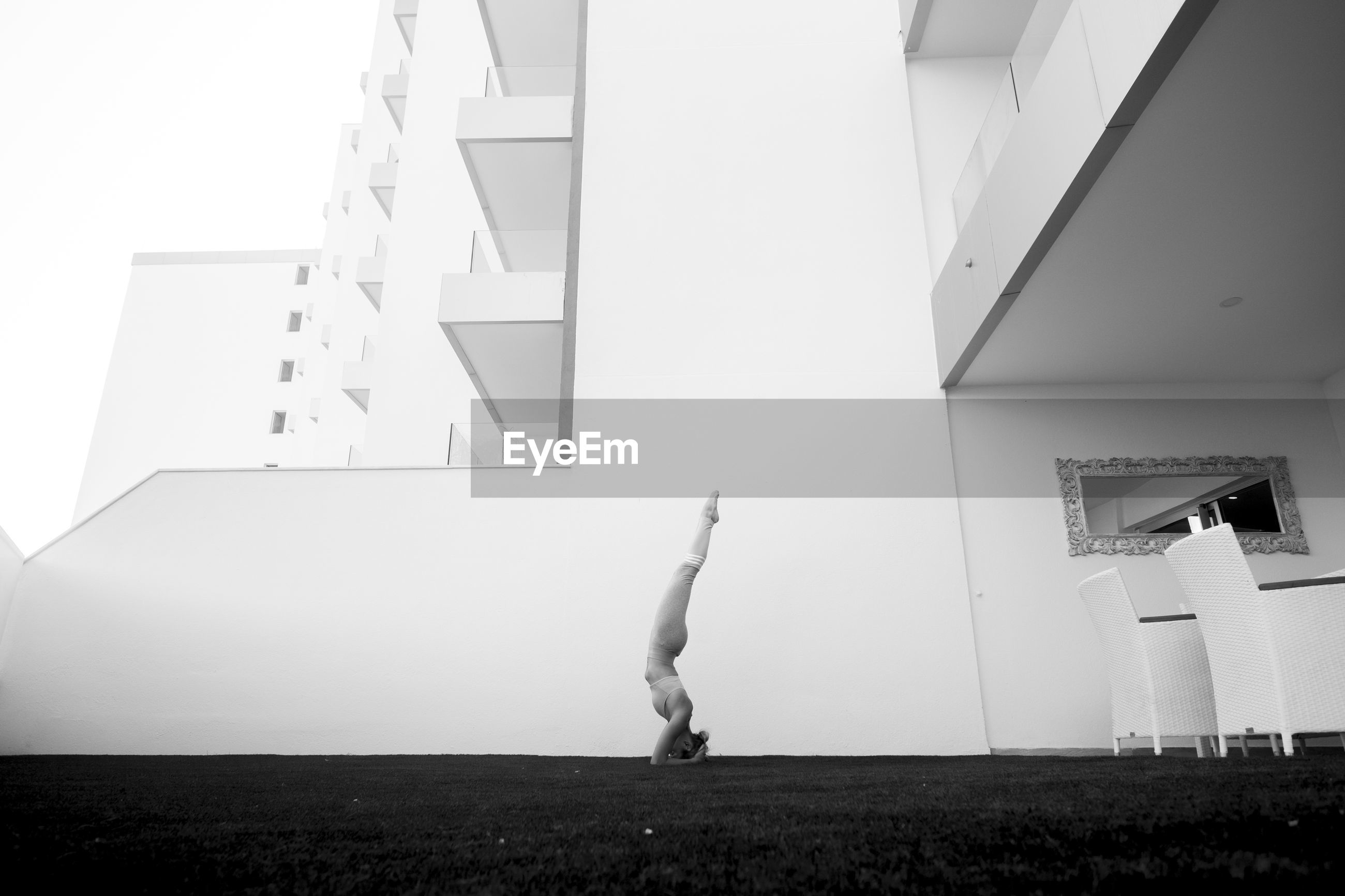 Side view of woman practicing headstand against building