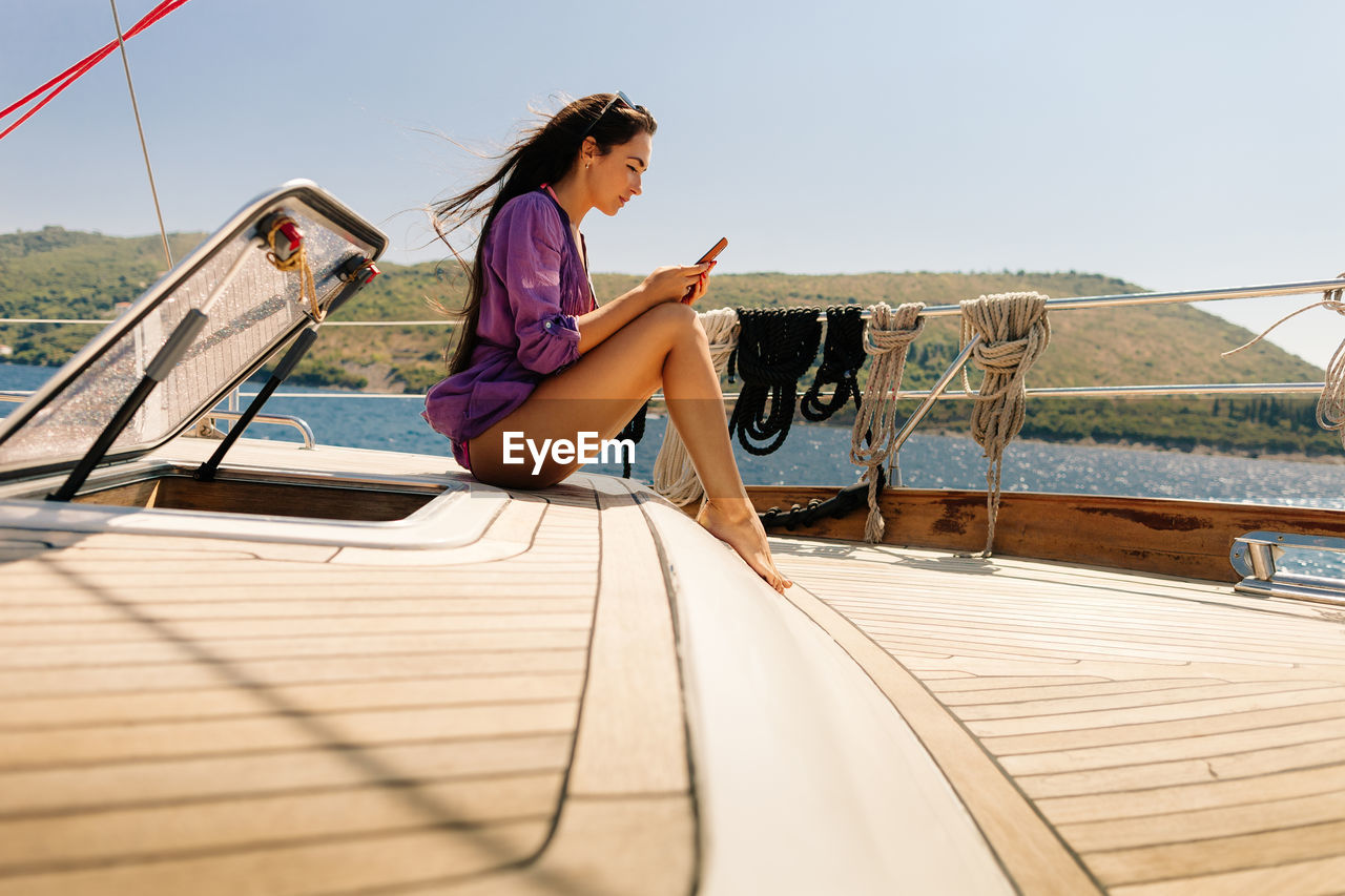 Young Woman On Boat Sailing In Sea Against Clear Sky