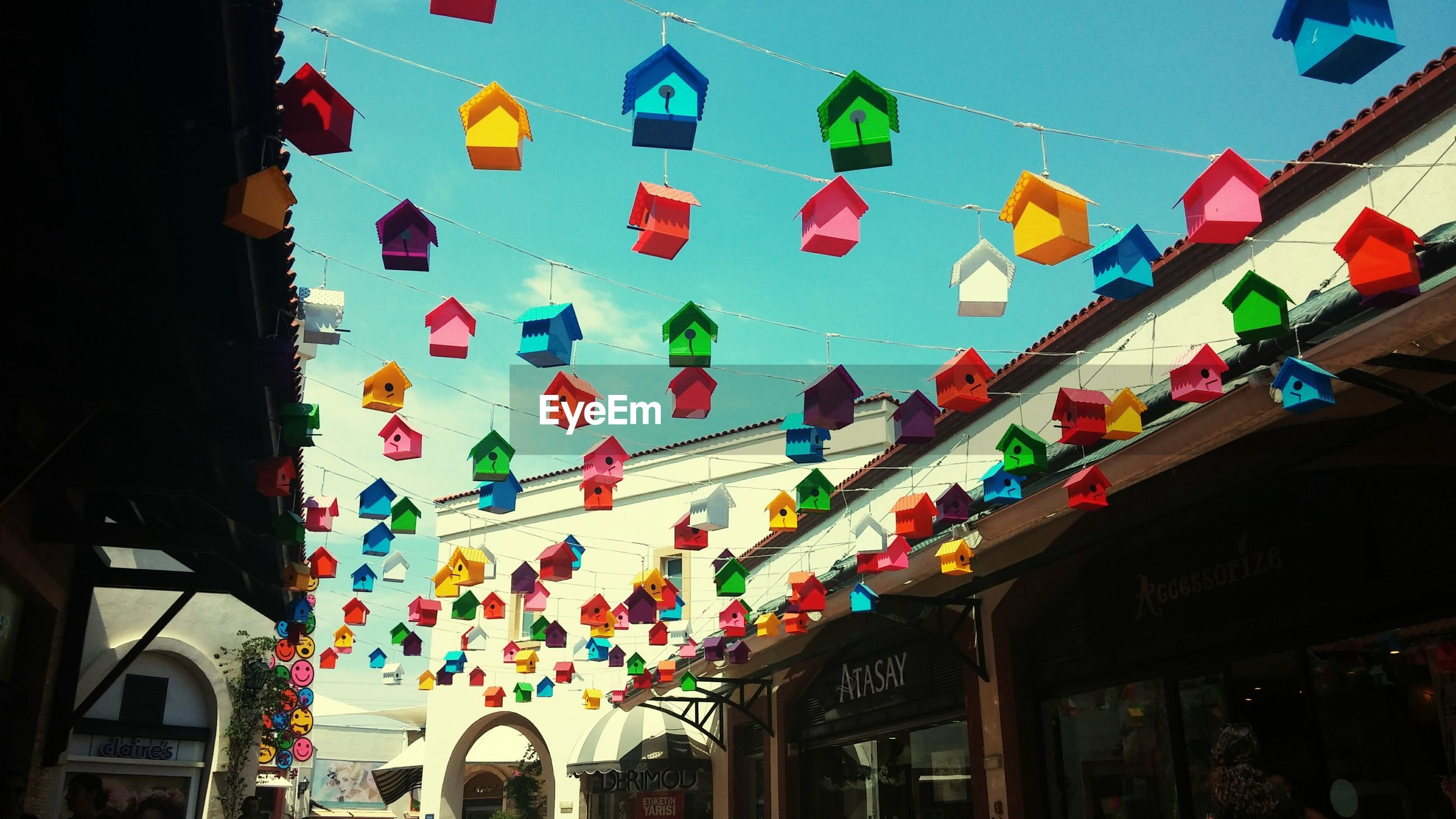 architecture, built structure, building exterior, low angle view, multi colored, hanging, flag, decoration, sky, lantern, window, building, city, lighting equipment, street light, blue, residential building, day, outdoors, in a row