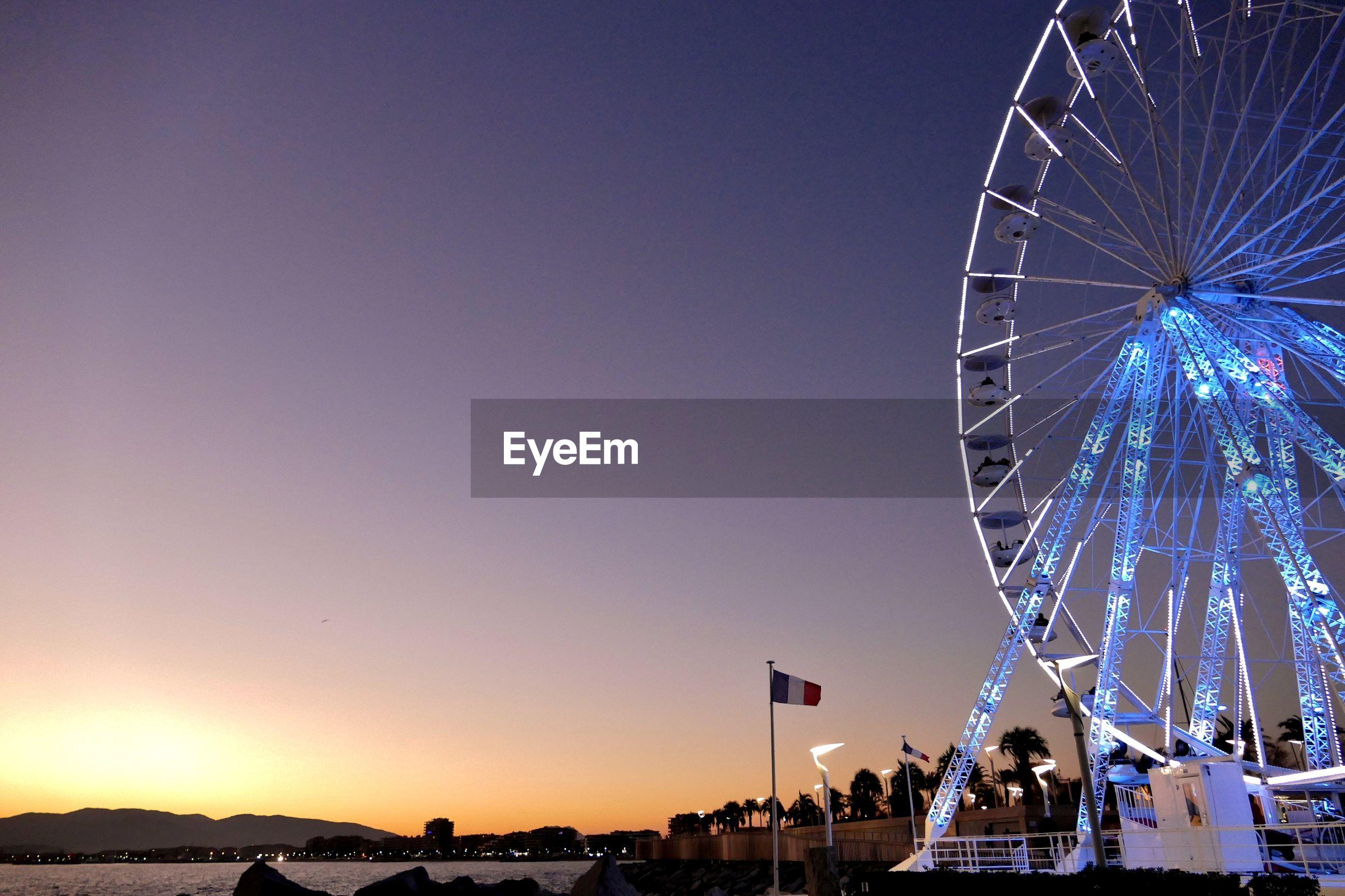 Illuminated ferris wheel against clear sky at sunset