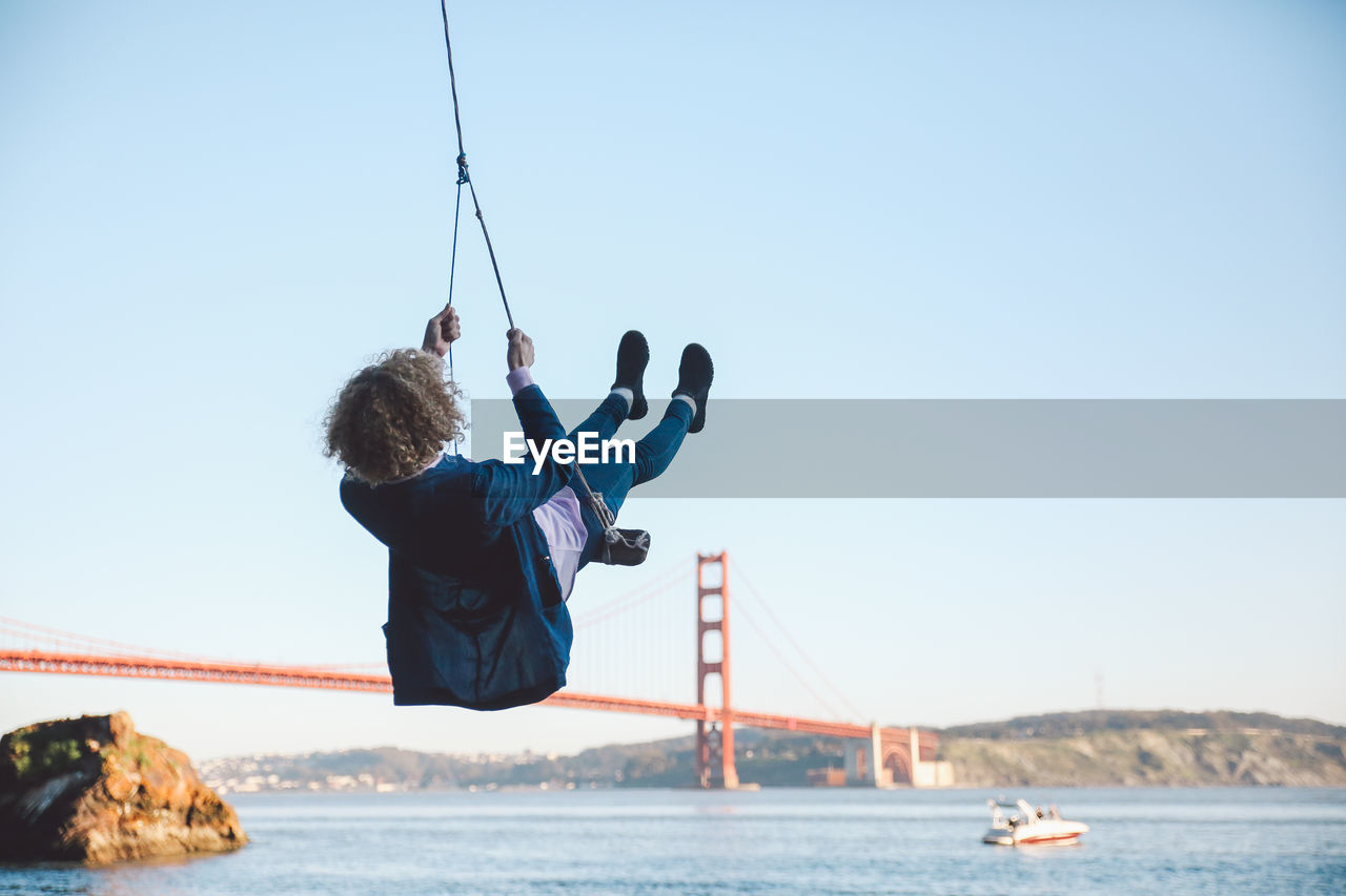 Rear View Of Mid Adult Woman Swinging At Beach Against Sky