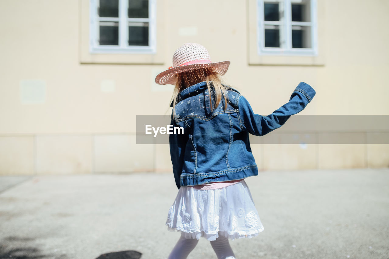 built structure, architecture, building exterior, one person, clothing, real people, child, women, leisure activity, hat, focus on foreground, three quarter length, childhood, girls, lifestyles, females, standing, day, building, casual clothing, outdoors, obscured face, innocence