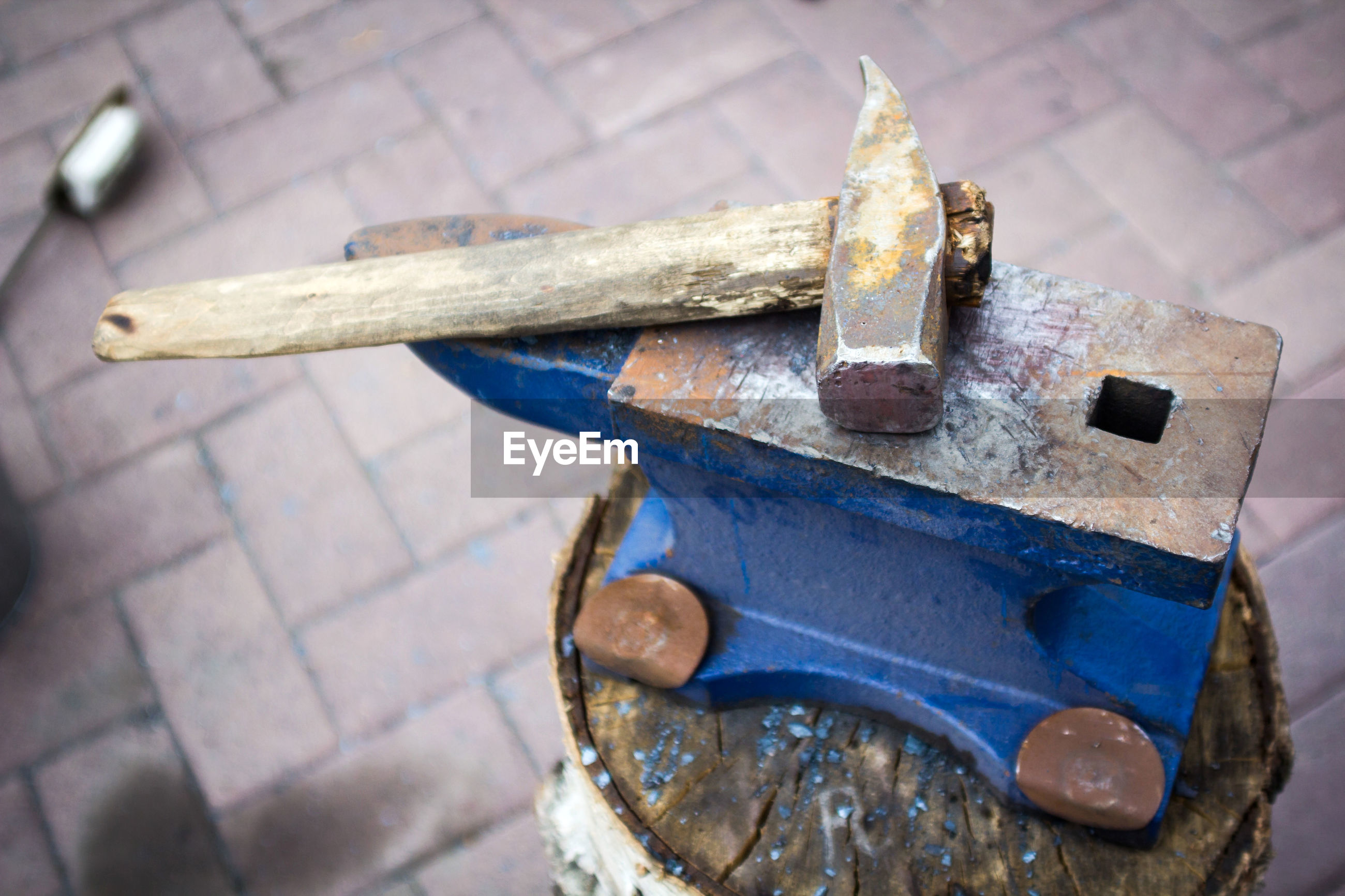 High angle view of hammer and metallic tool on tree stump
