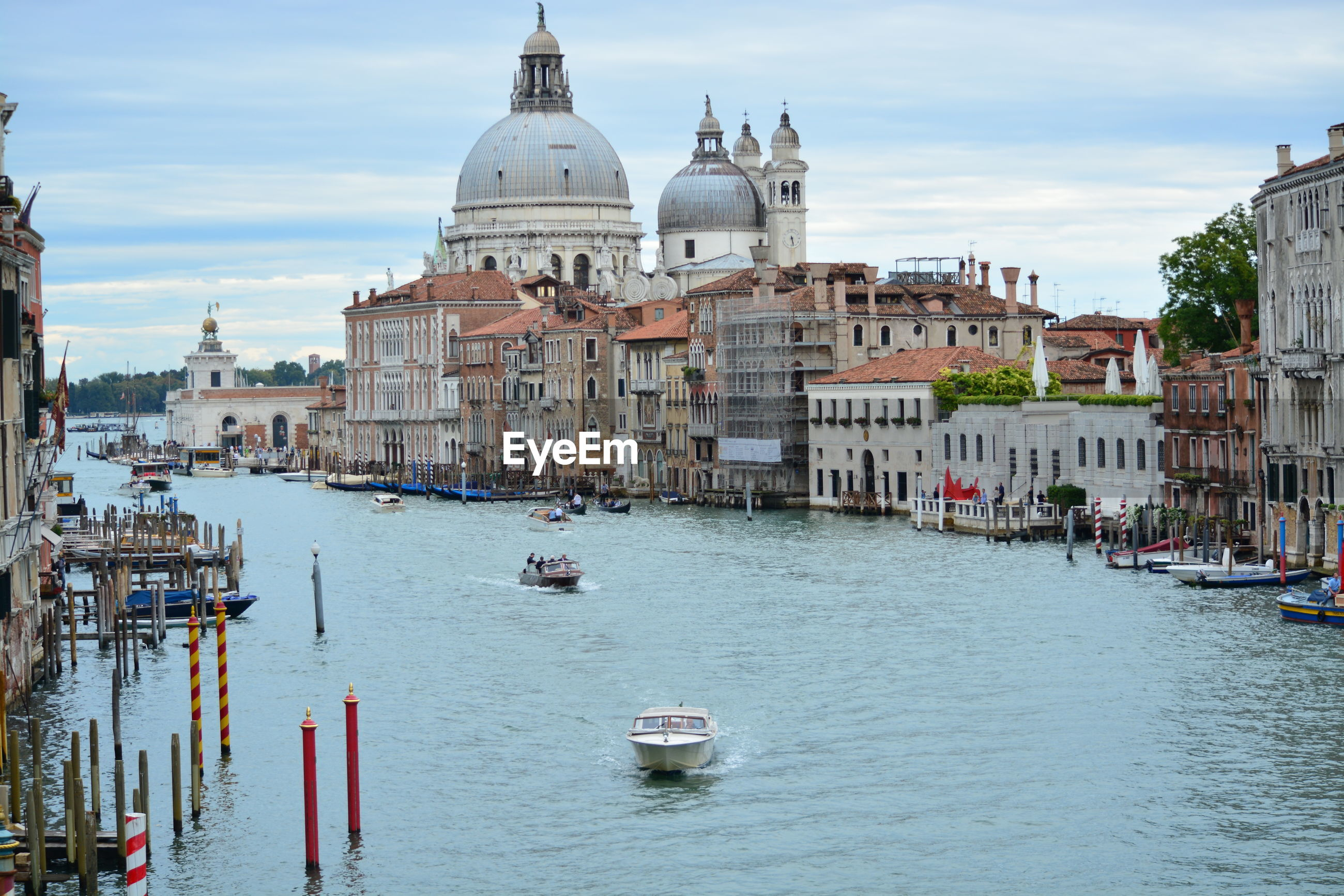 Boats in grand canal with historic santa maria della salute against sky