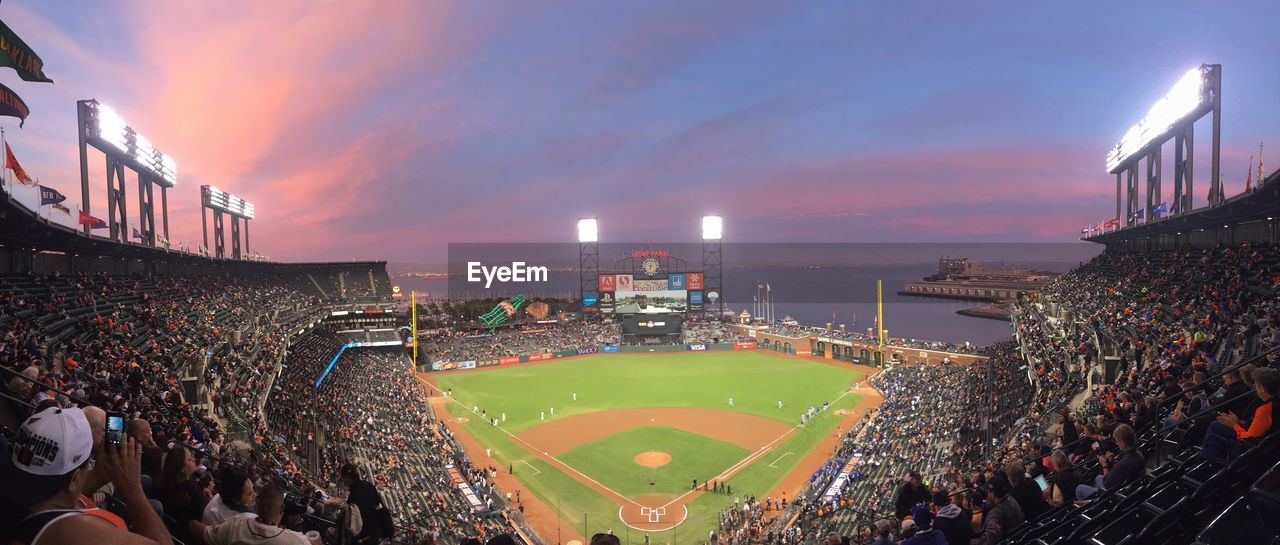 Spectators at baseball stadium during dusk