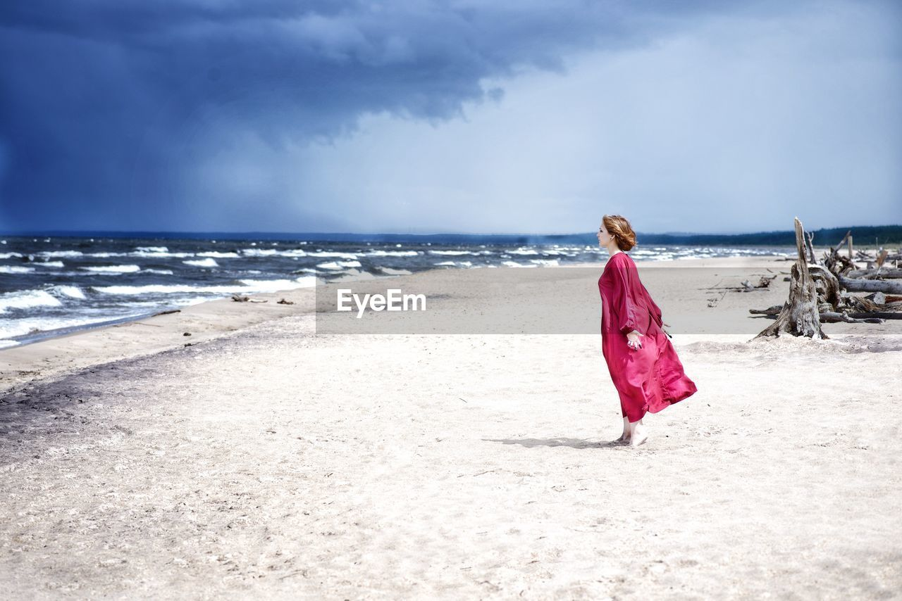 Side view of woman standing at beach against sky