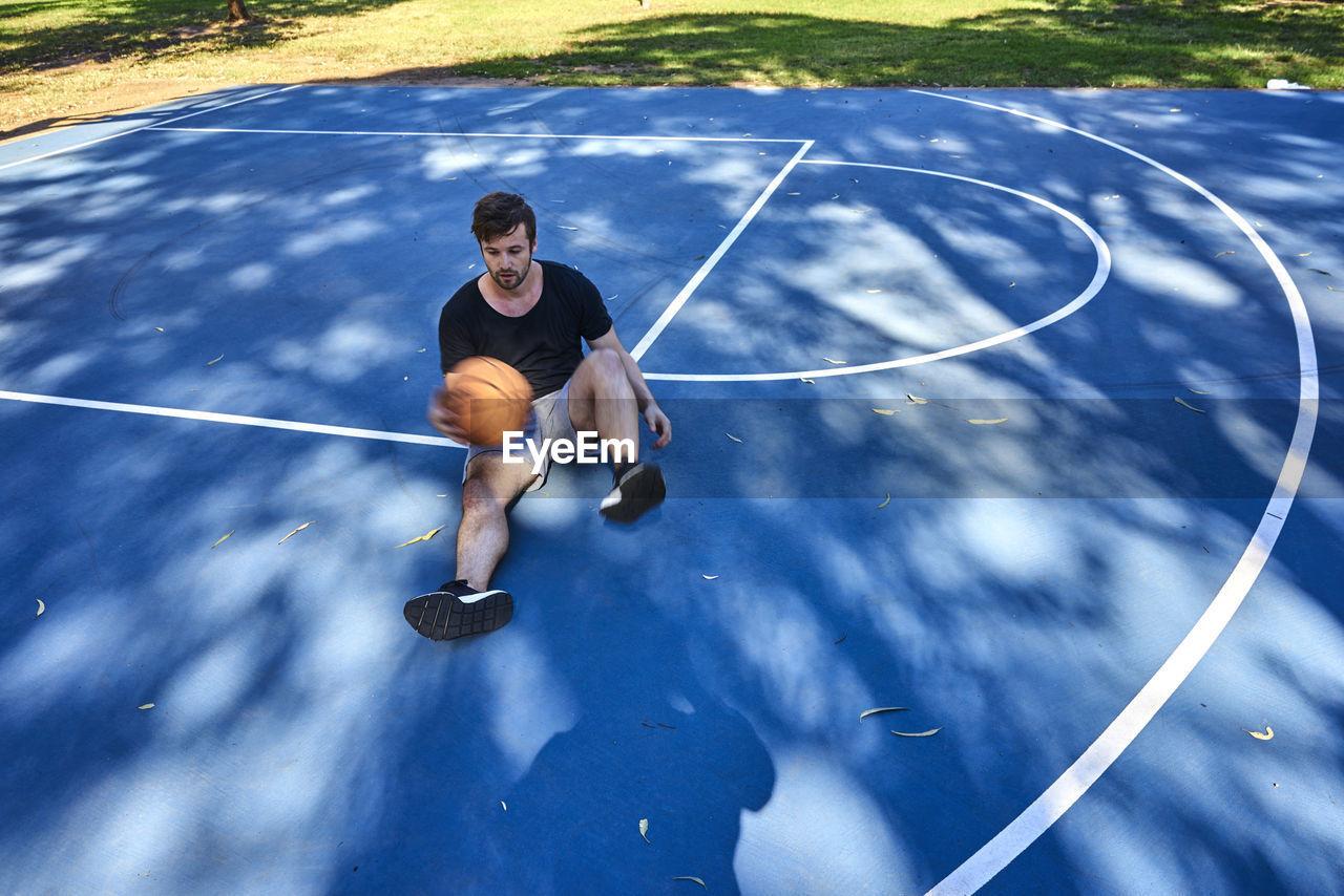 Full Length Of Man Sitting On Basketball Court