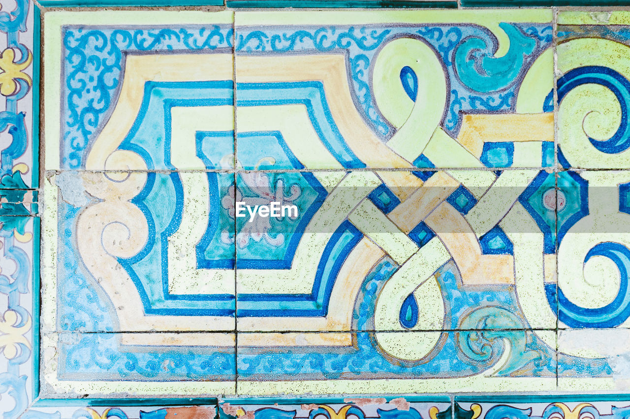 blue, art and craft, full frame, pattern, text, close-up, no people, creativity, design, craft, tile, flooring, wall - building feature, western script, wood - material, ornate, mosaic, indoors, backgrounds, architecture, tiled floor
