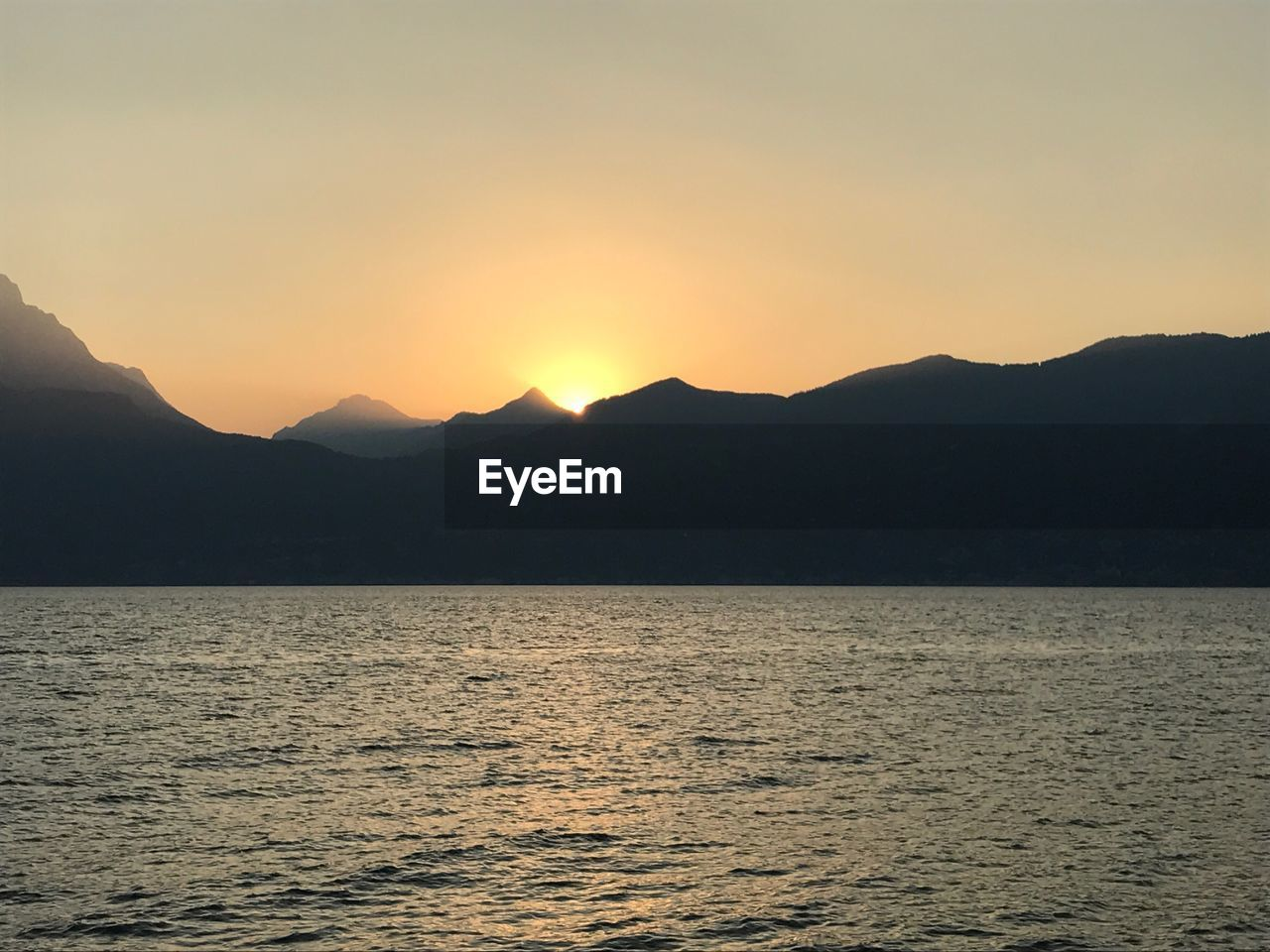 mountain, sunset, nature, beauty in nature, silhouette, tranquility, scenics, tranquil scene, water, mountain range, sea, no people, waterfront, outdoors, sky, clear sky, scenery, day