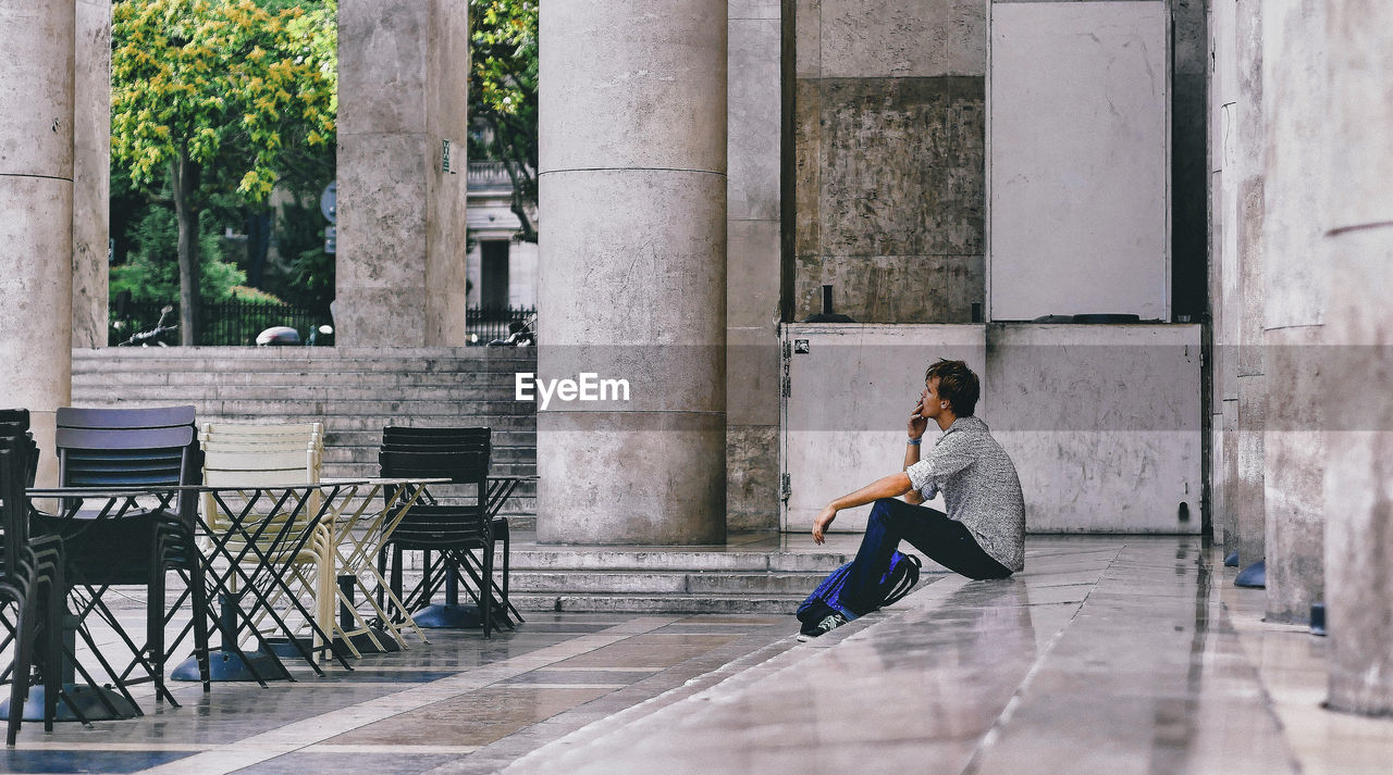 one person, sitting, full length, real people, architecture, seat, casual clothing, side view, built structure, lifestyles, leisure activity, day, young adult, outdoors, relaxation, building exterior, table, architectural column, bench, contemplation