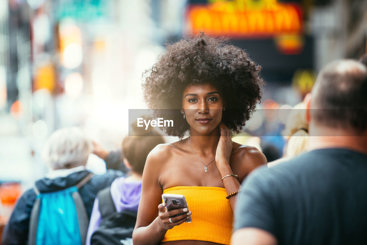 Portrait Of Confident Young Woman Holding Smart Phone On City Street