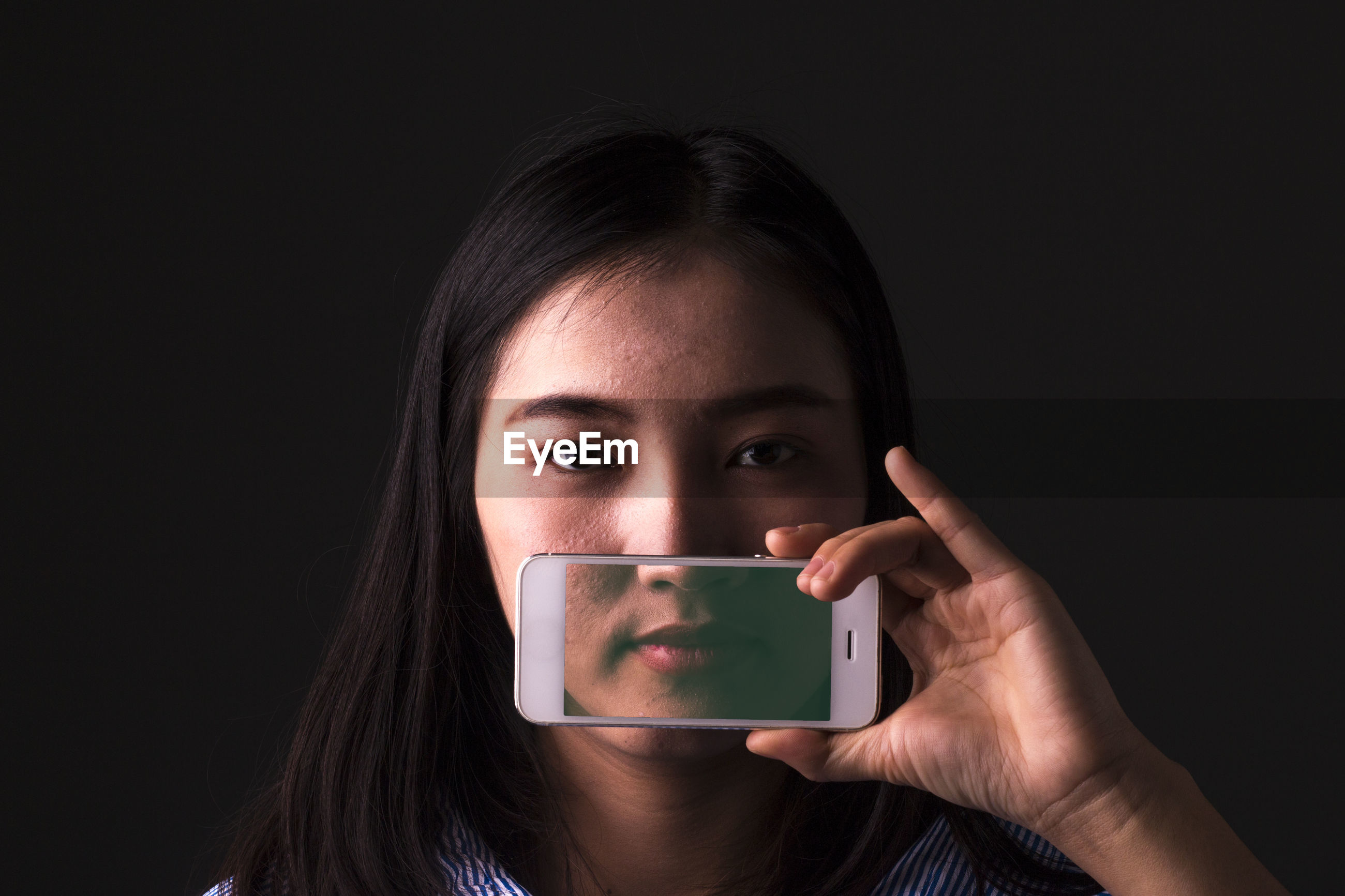 Close-up portrait of woman holding mobile phone against black background