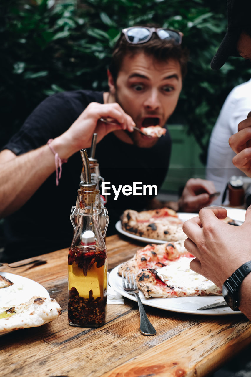 Men eating food on table against trees