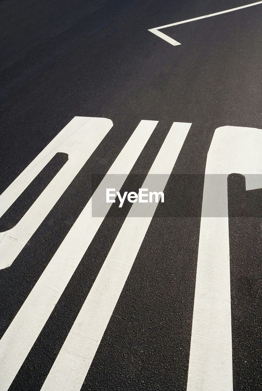 road marking, transportation, road, asphalt, guidance, striped, high angle view, street, direction, no people, white line, road sign, communication, outdoors, parking sign, day, close-up