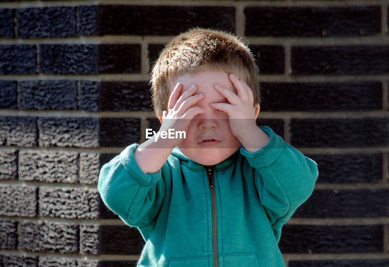 Close-up of boy with hands covering eyes standing by wall