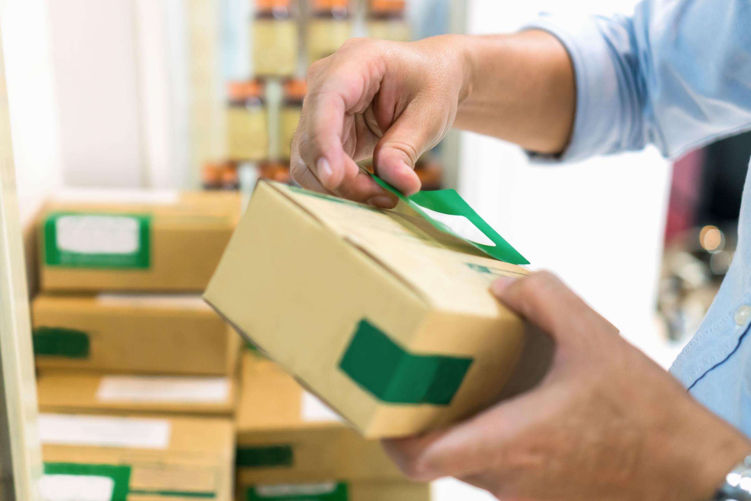 Cropped hands of man sticking labels on cardboard boxes at workshop