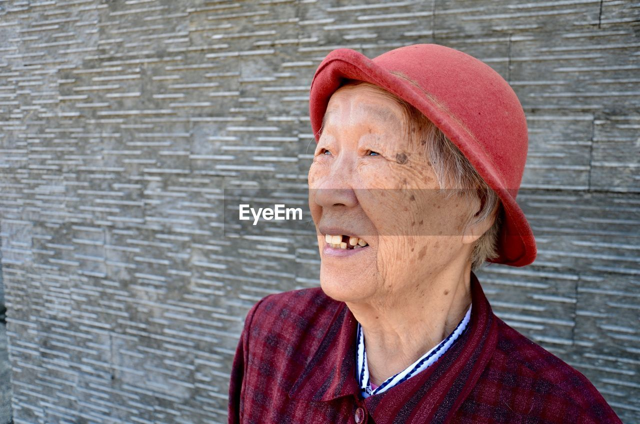 Close-up of senior woman standing against wall