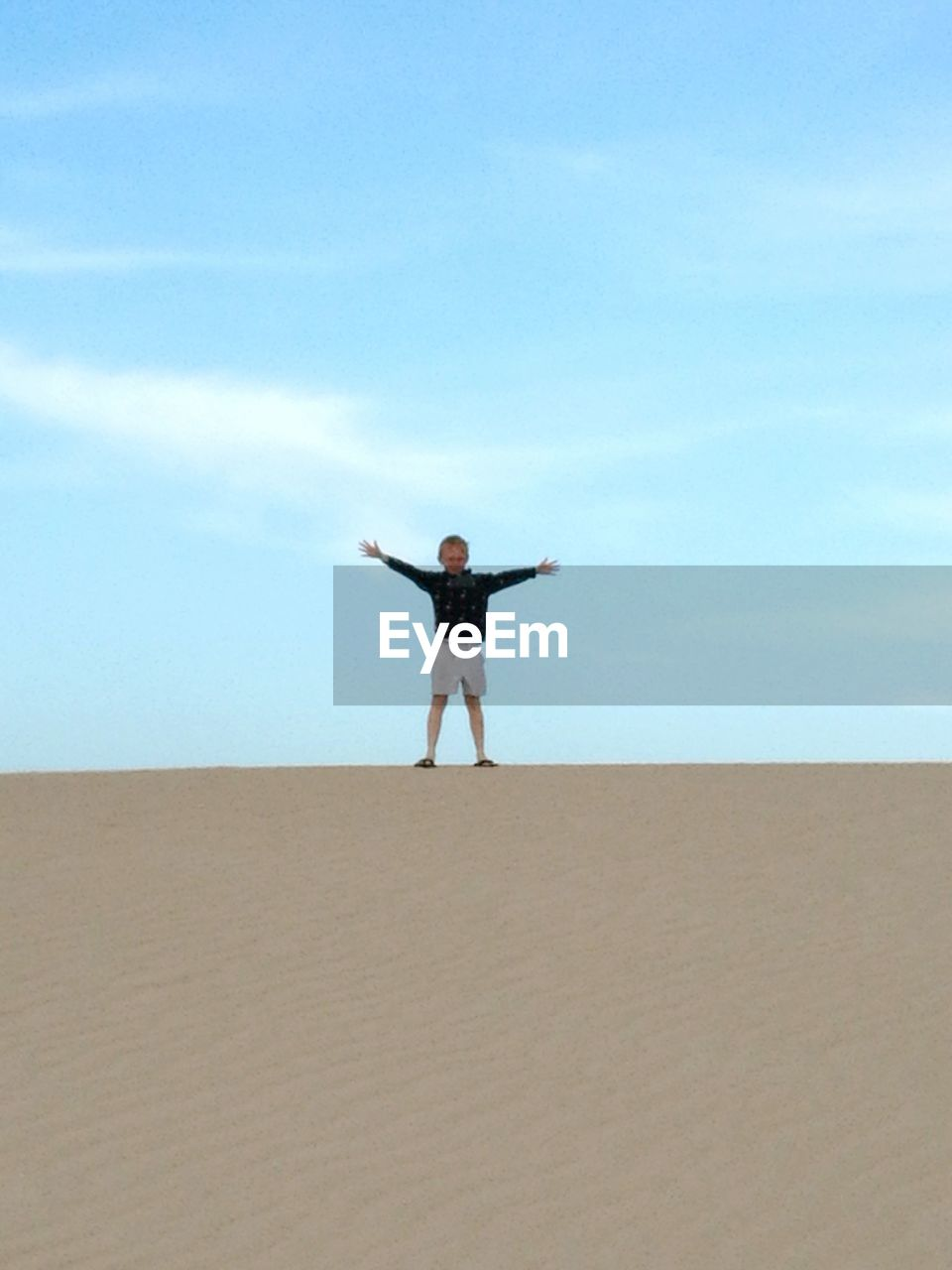 arms raised, sand, sky, one person, arms outstretched, standing, human arm, day, nature, blue, outdoors, beach, leisure activity, real people, human body part, full length, scenics, beauty in nature, energetic, young adult, people
