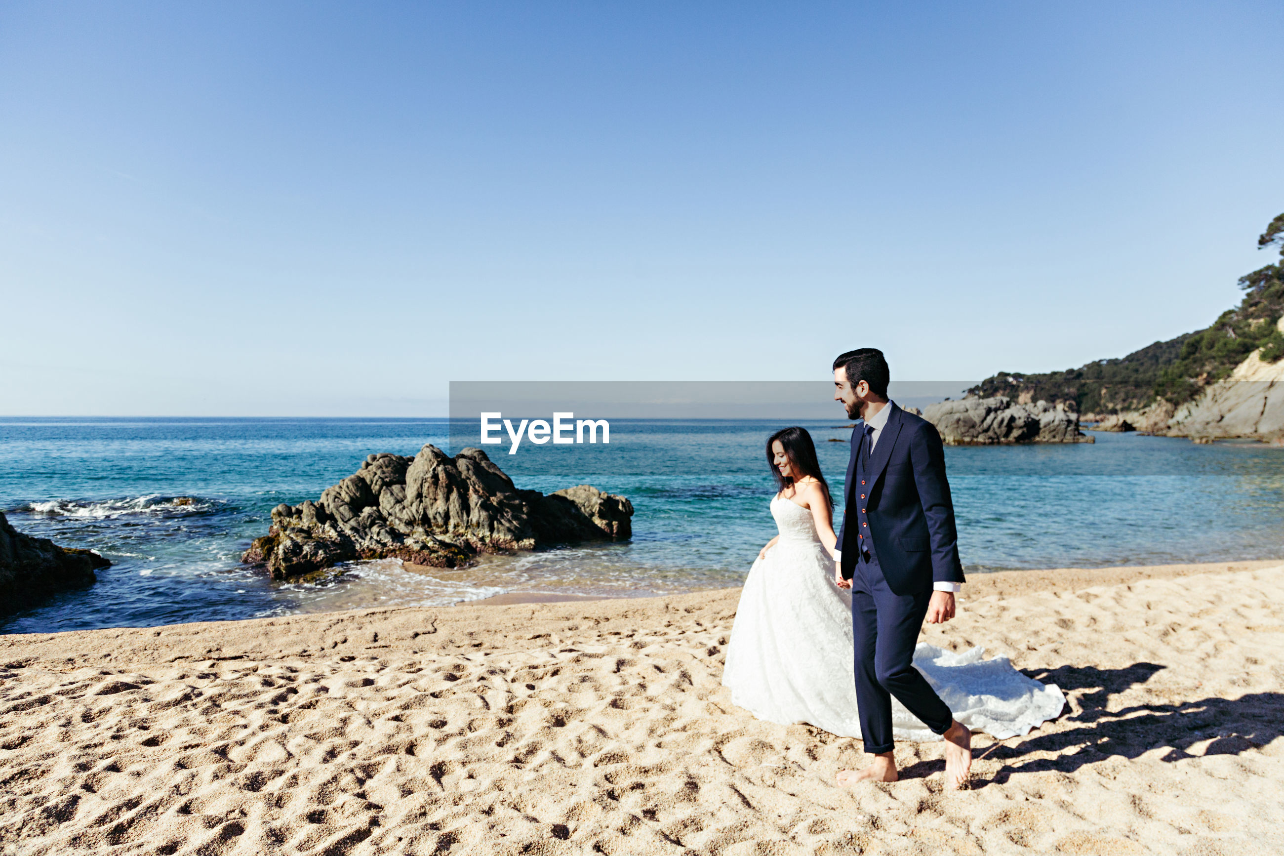 Newlywed couple walking at beach against clear sky during sunny day