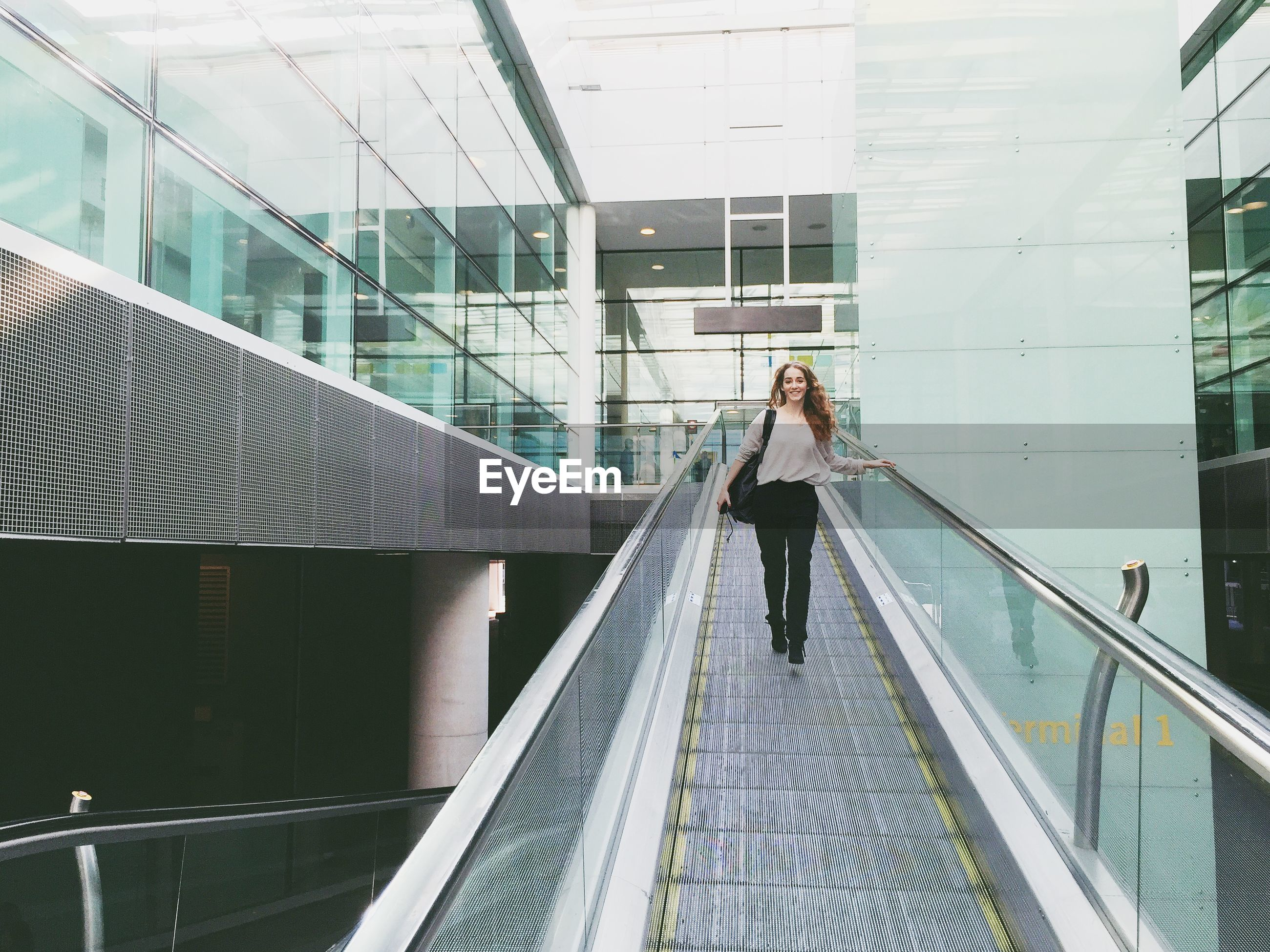 Young woman walking on moving walkway in building