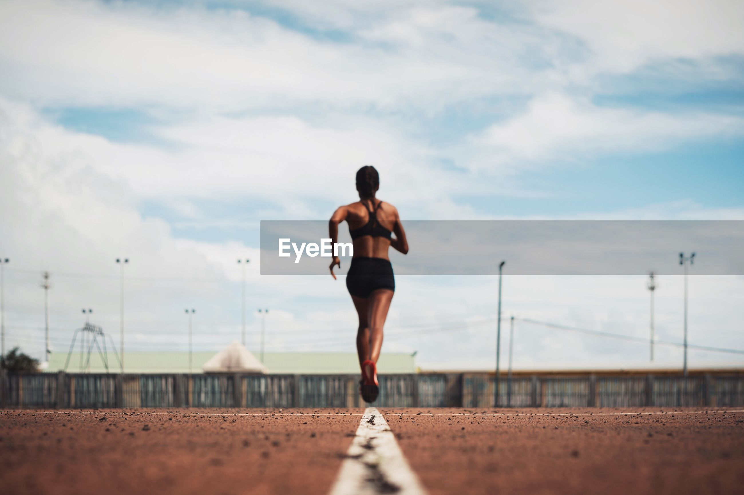 Rear view of female athlete running on track field against sky