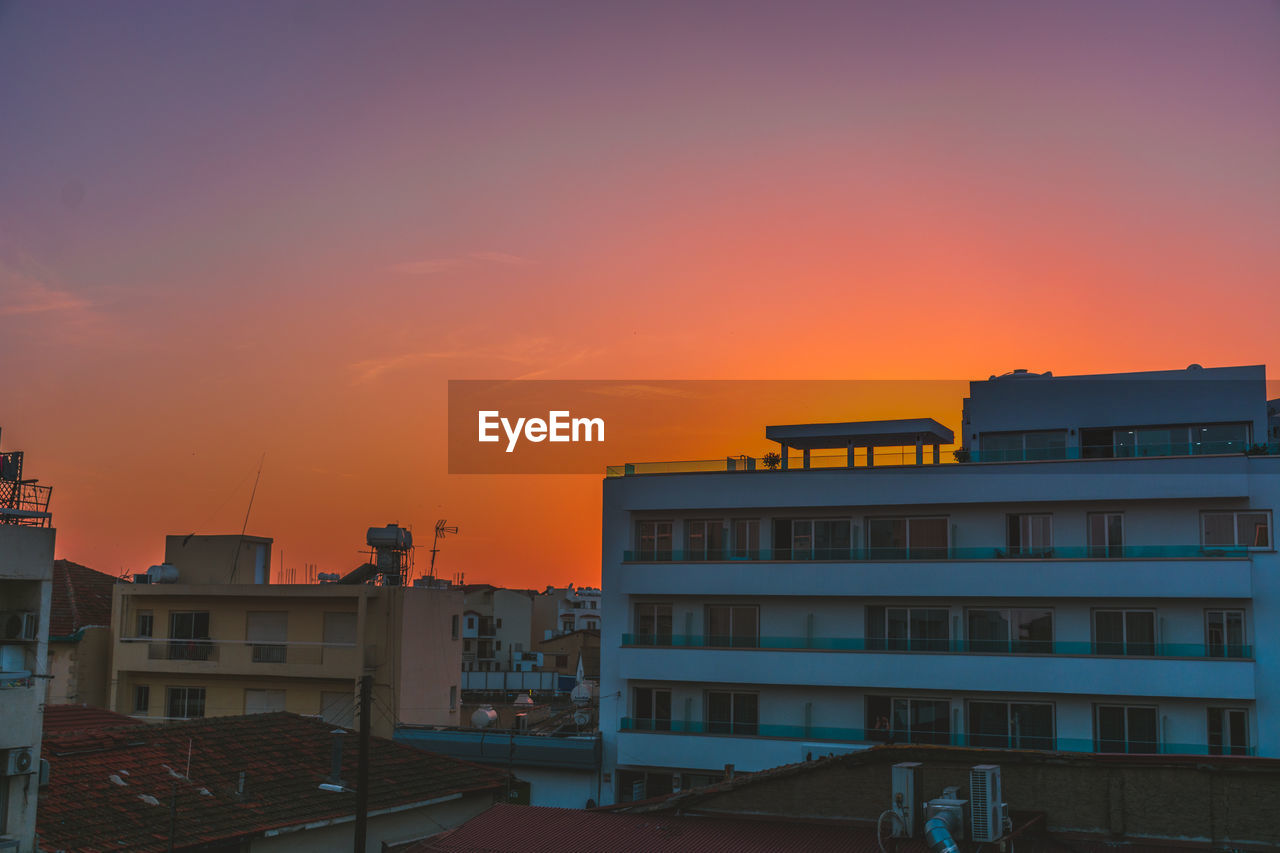 building exterior, built structure, architecture, sunset, sky, building, orange color, residential district, city, nature, no people, outdoors, cloud - sky, house, water, copy space, roof, town, beauty in nature, sun, apartment