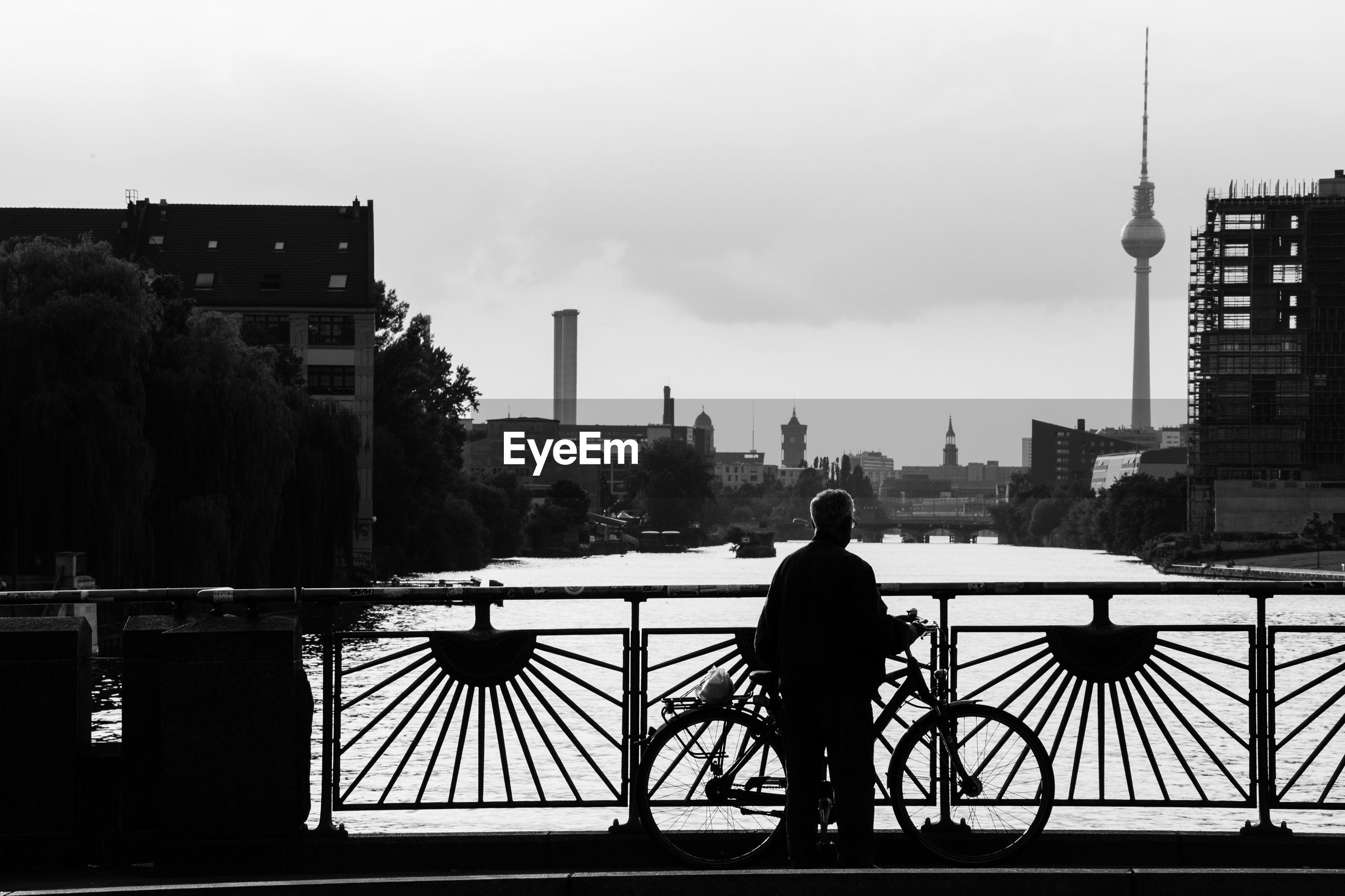 REAR VIEW OF MAN STANDING ON RAILING WITH CITY IN BACKGROUND