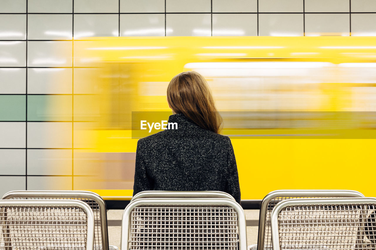 Rear View Of Young Woman Waiting For Subway