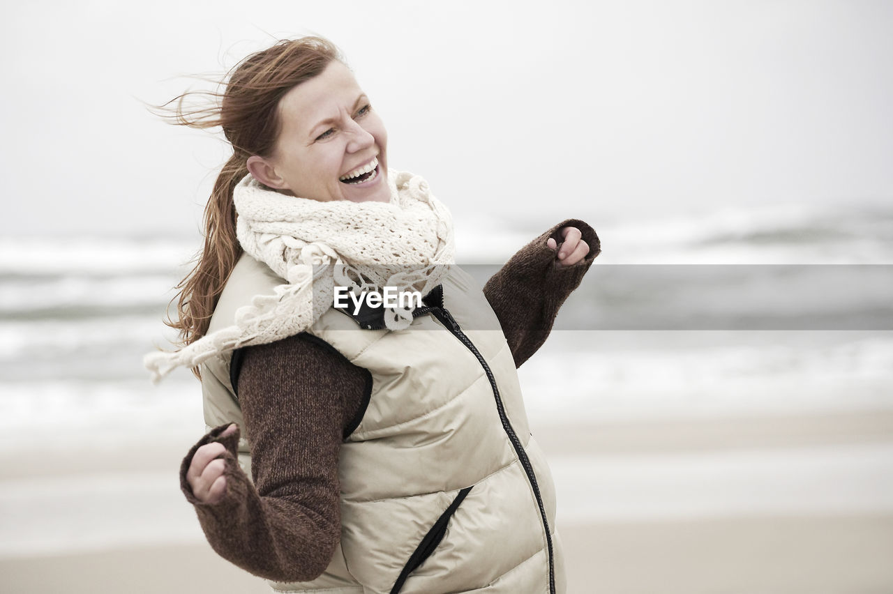 PORTRAIT OF SMILING WOMAN ON BEACH DURING WINTER