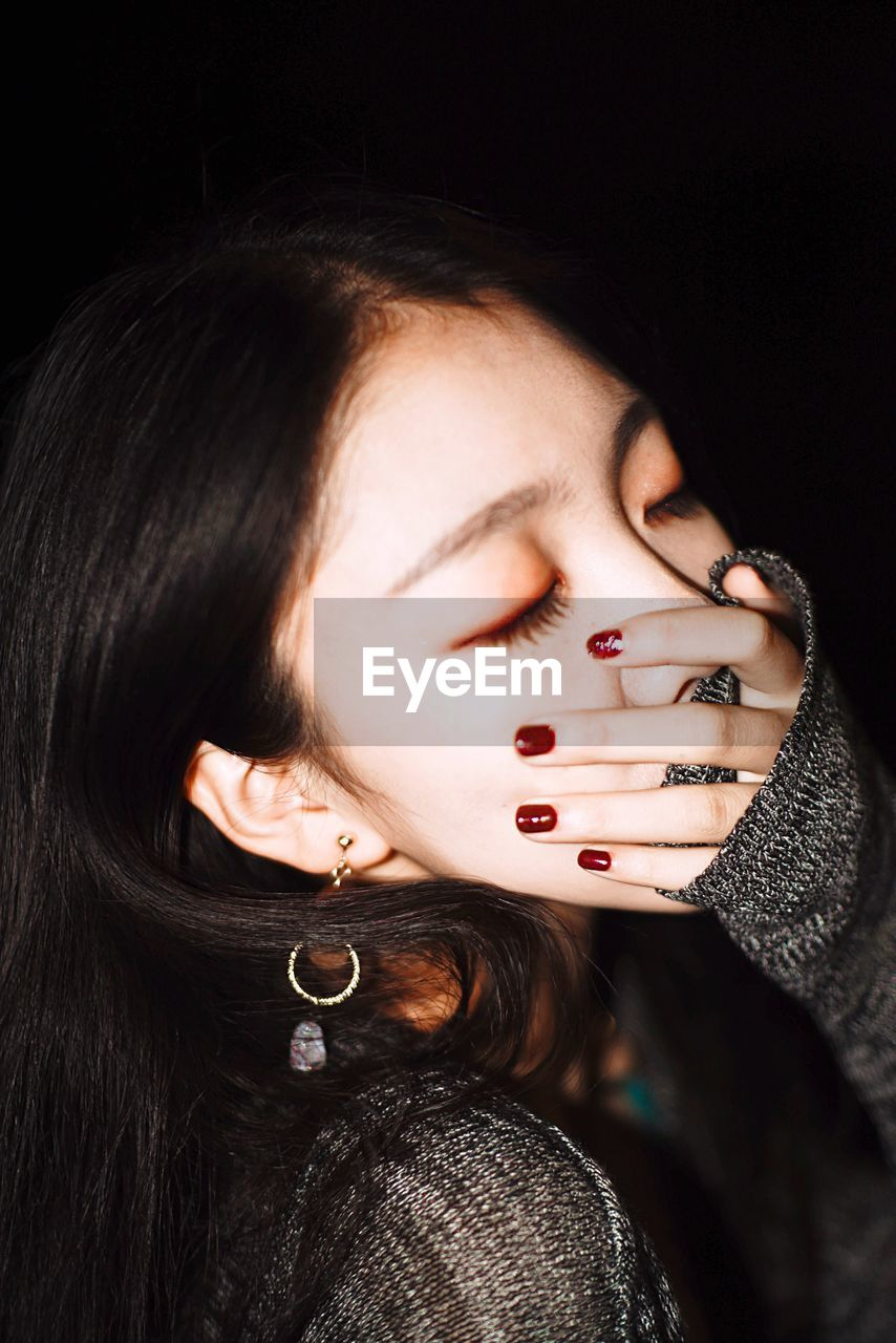 Woman Covering Mouth With Hand Against Black Background