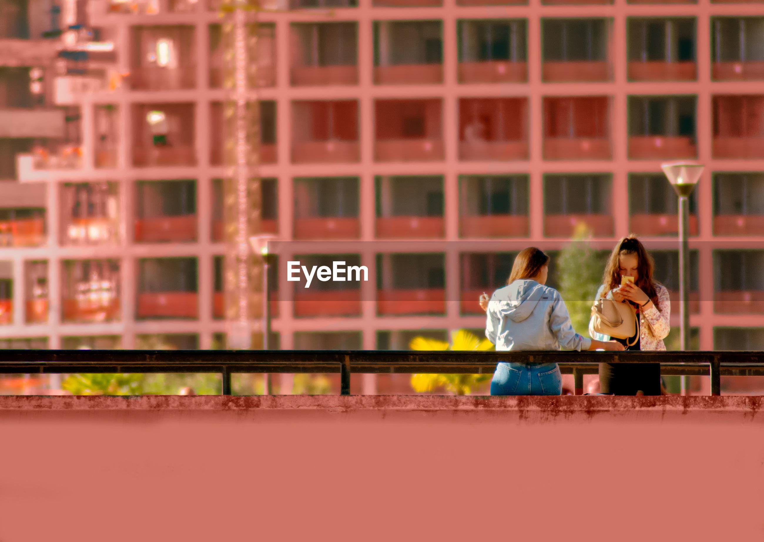 Rear view of couple sitting on bridge