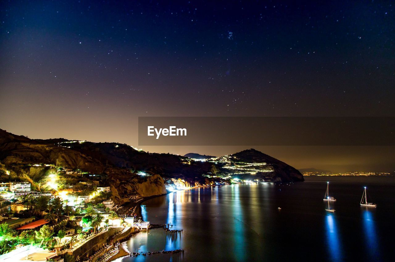 water, night, sky, star - space, scenics - nature, beauty in nature, illuminated, reflection, nature, no people, building exterior, architecture, sea, tranquil scene, built structure, star, tranquility, mountain, waterfront, astronomy, outdoors