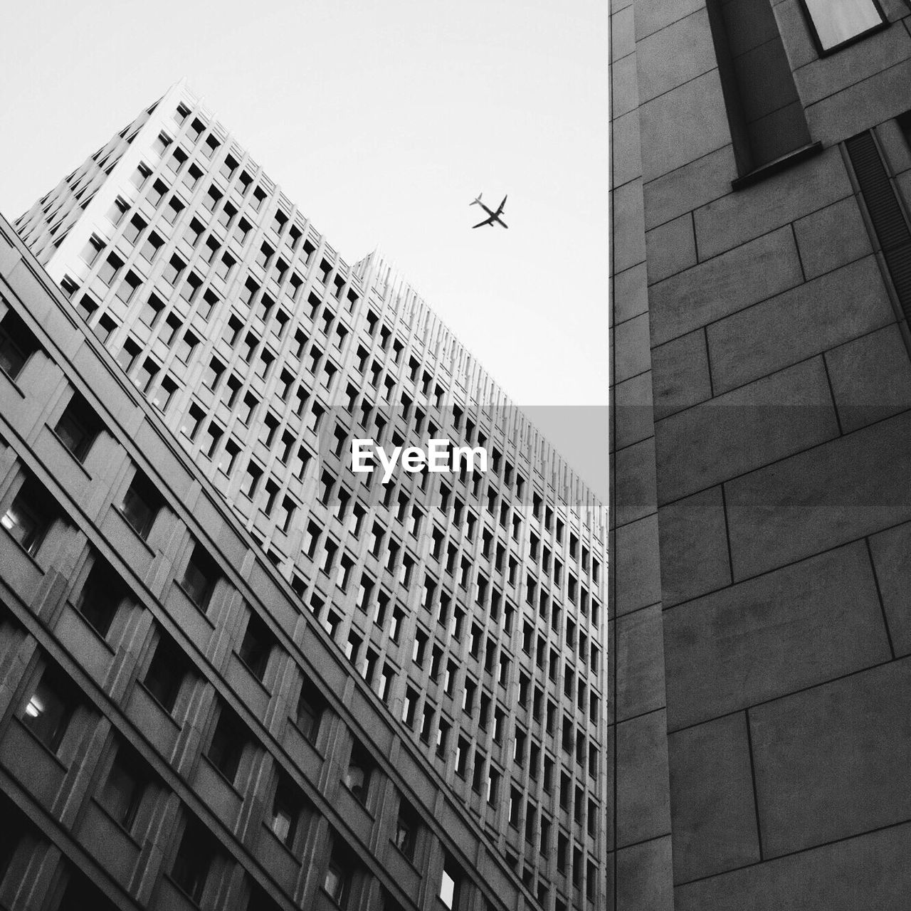 flying, airplane, architecture, low angle view, building exterior, built structure, skyscraper, city, transportation, day, tall, outdoors, no people, sky