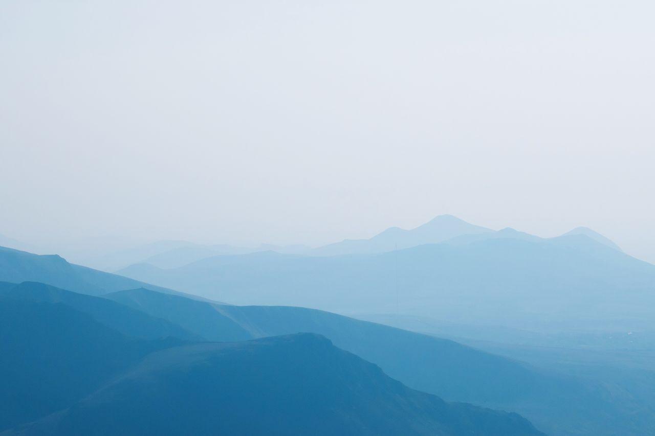 mountain, beauty in nature, scenics - nature, tranquil scene, tranquility, mountain range, sky, copy space, fog, non-urban scene, environment, idyllic, no people, landscape, nature, majestic, remote, day, outdoors, mountain peak, mountain ridge, hazy