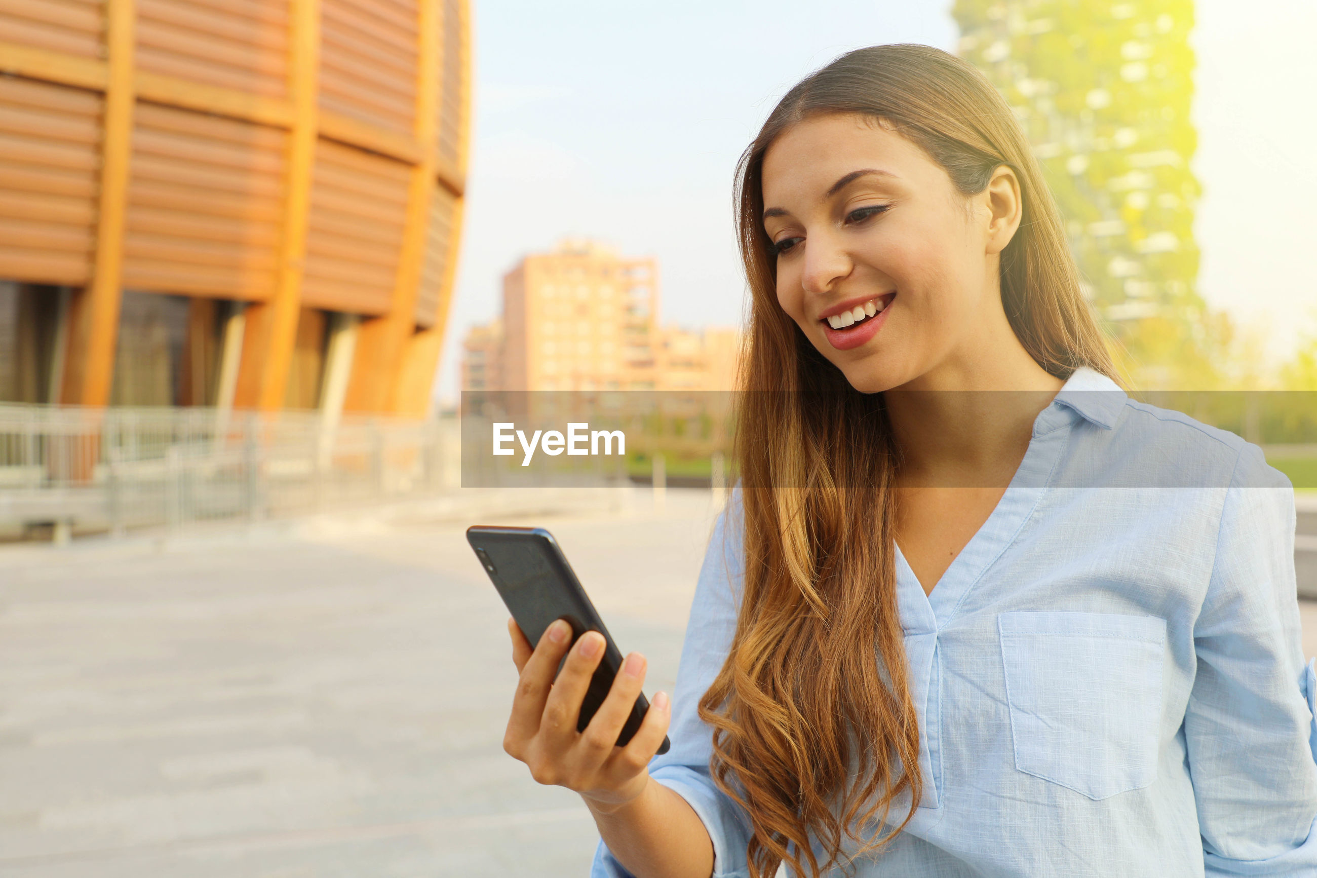 Smiling young woman using mobile phone while standing in city