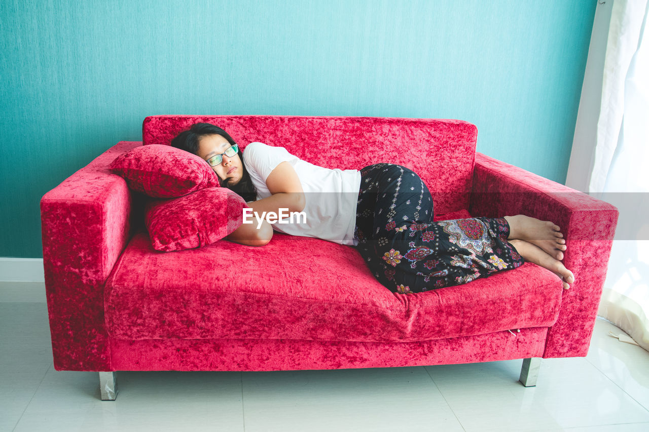 furniture, relaxation, red, indoors, sofa, full length, real people, home interior, one person, lifestyles, lying down, pillow, comfortable, leisure activity, women, domestic room, cushion, high angle view, resting, hairstyle