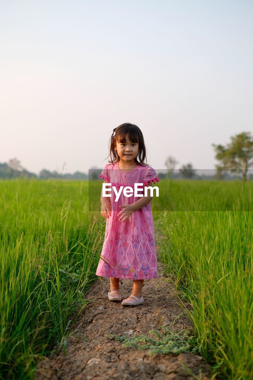 girls, childhood, child, grass, full length, plant, field, land, one person, women, innocence, females, sky, pink color, cute, nature, standing, real people, leisure activity, fashion, outdoors