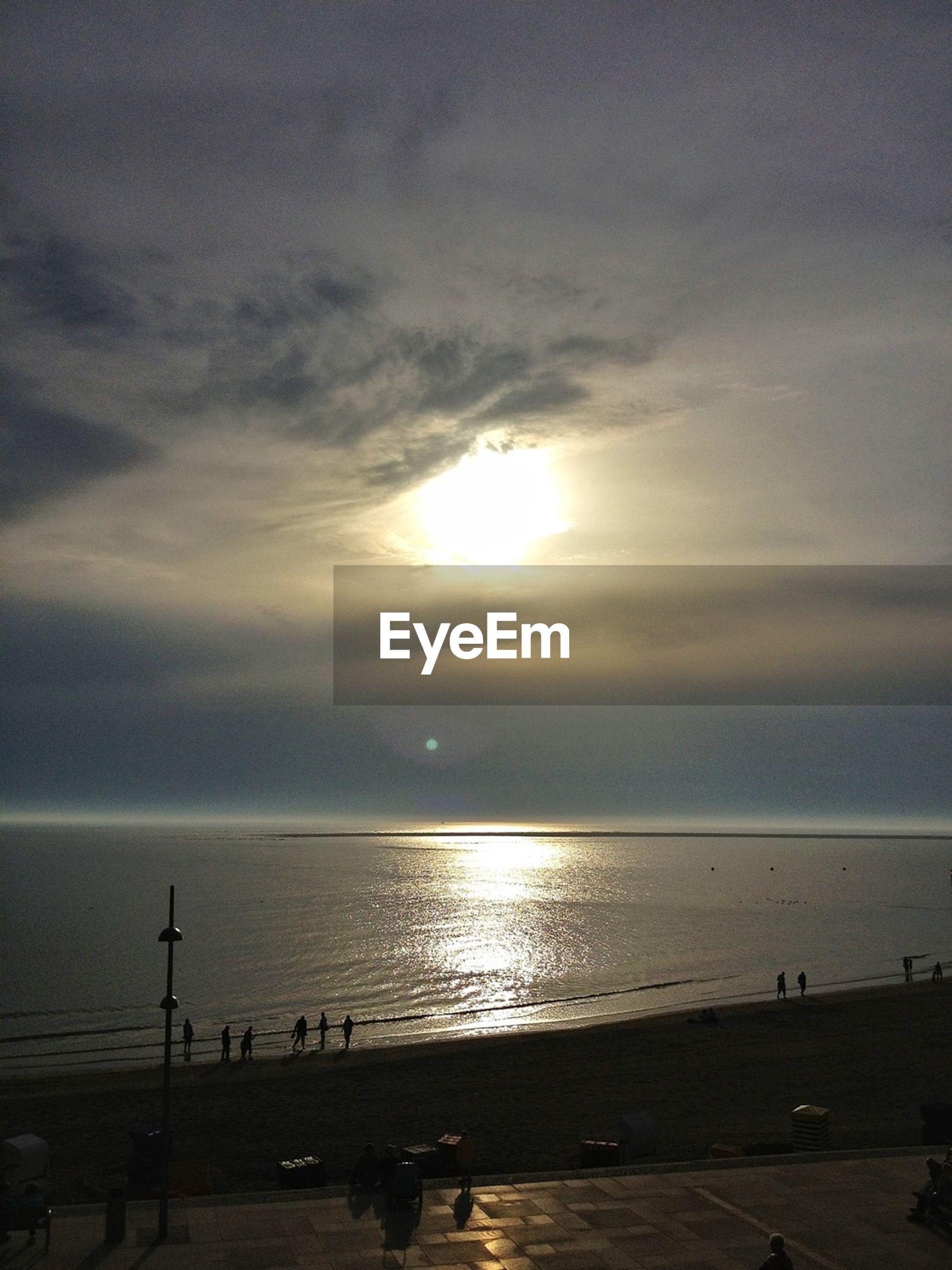 sea, horizon over water, water, beach, sunset, sun, sky, scenics, tranquil scene, beauty in nature, shore, tranquility, cloud - sky, silhouette, nature, idyllic, sunlight, reflection, incidental people, sunbeam