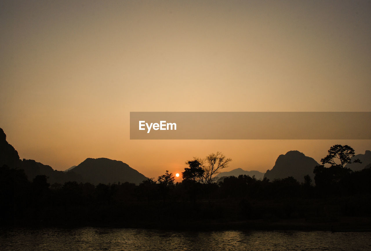 sunset, silhouette, mountain, orange color, scenics, lake, nature, tranquil scene, tranquility, beauty in nature, water, tree, outdoors, no people, sky, waterfront, mountain range, clear sky, landscape