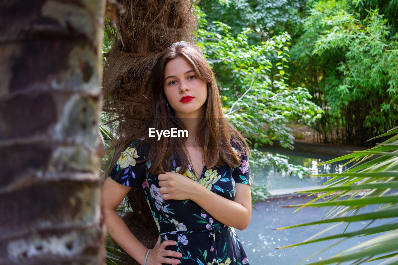Portrait of beautiful woman standing by tree trunk