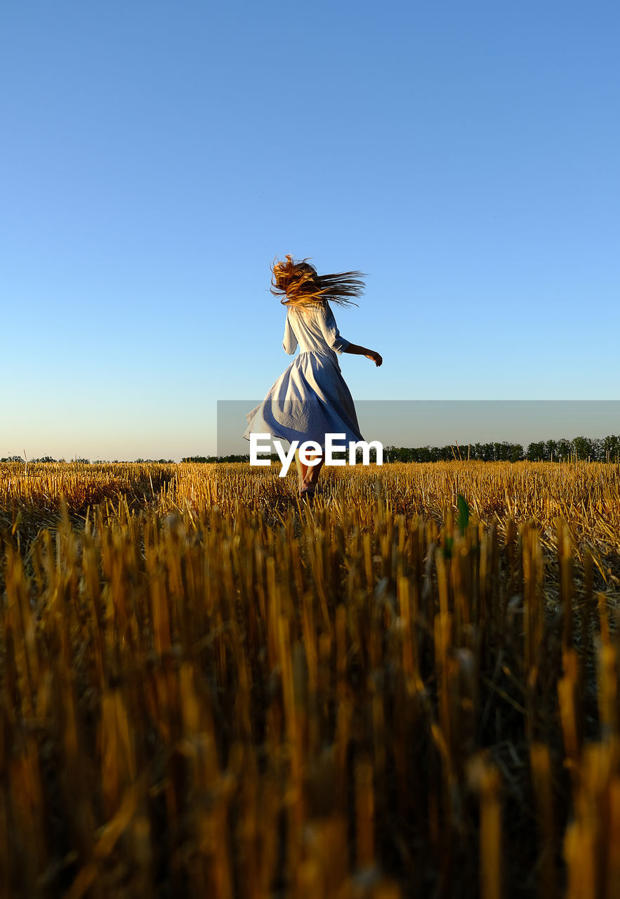 Woman standing on land against clear sky