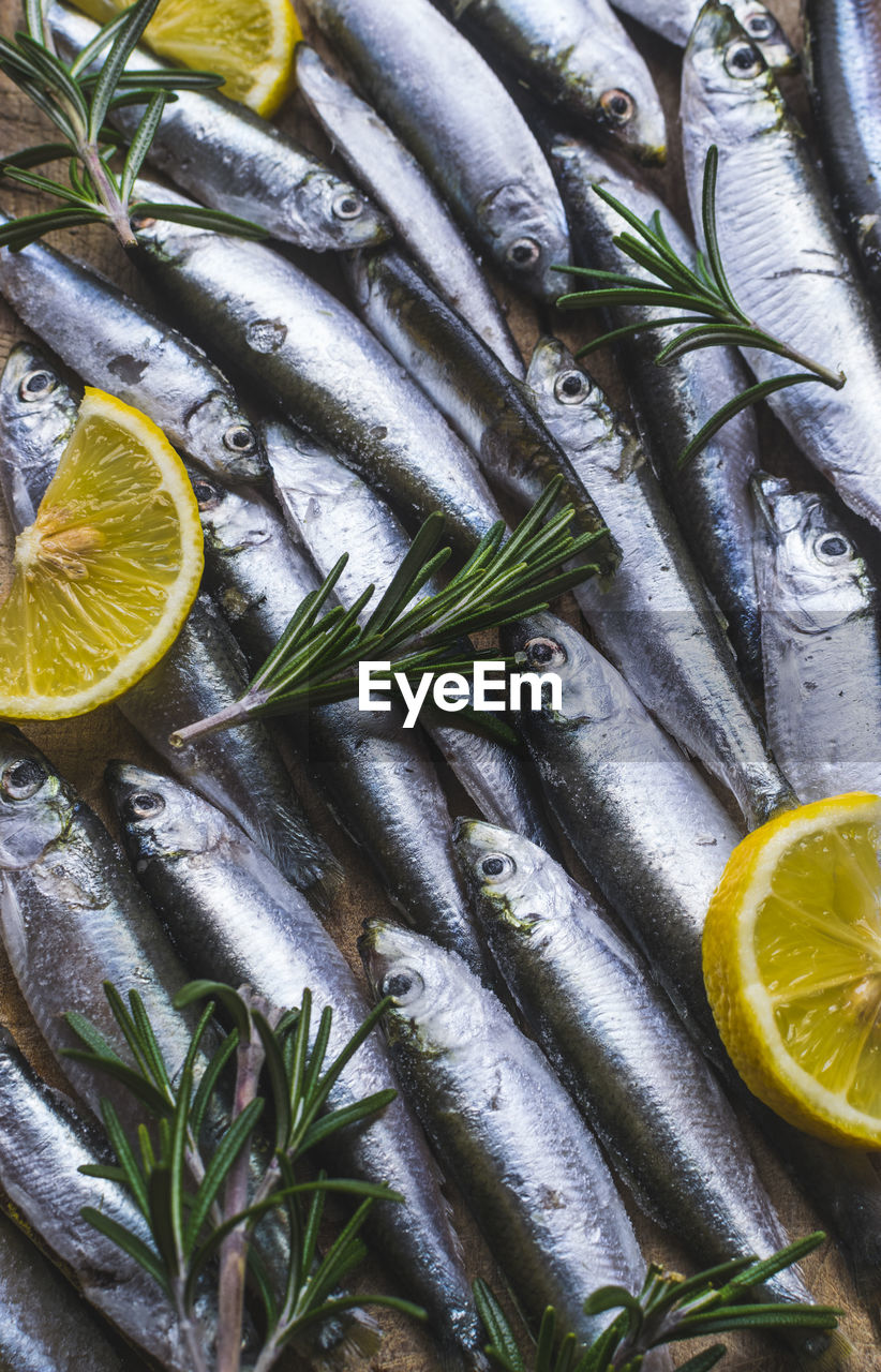 High Angle View Of Fishes And Lemon Slices With Rosemary On Table