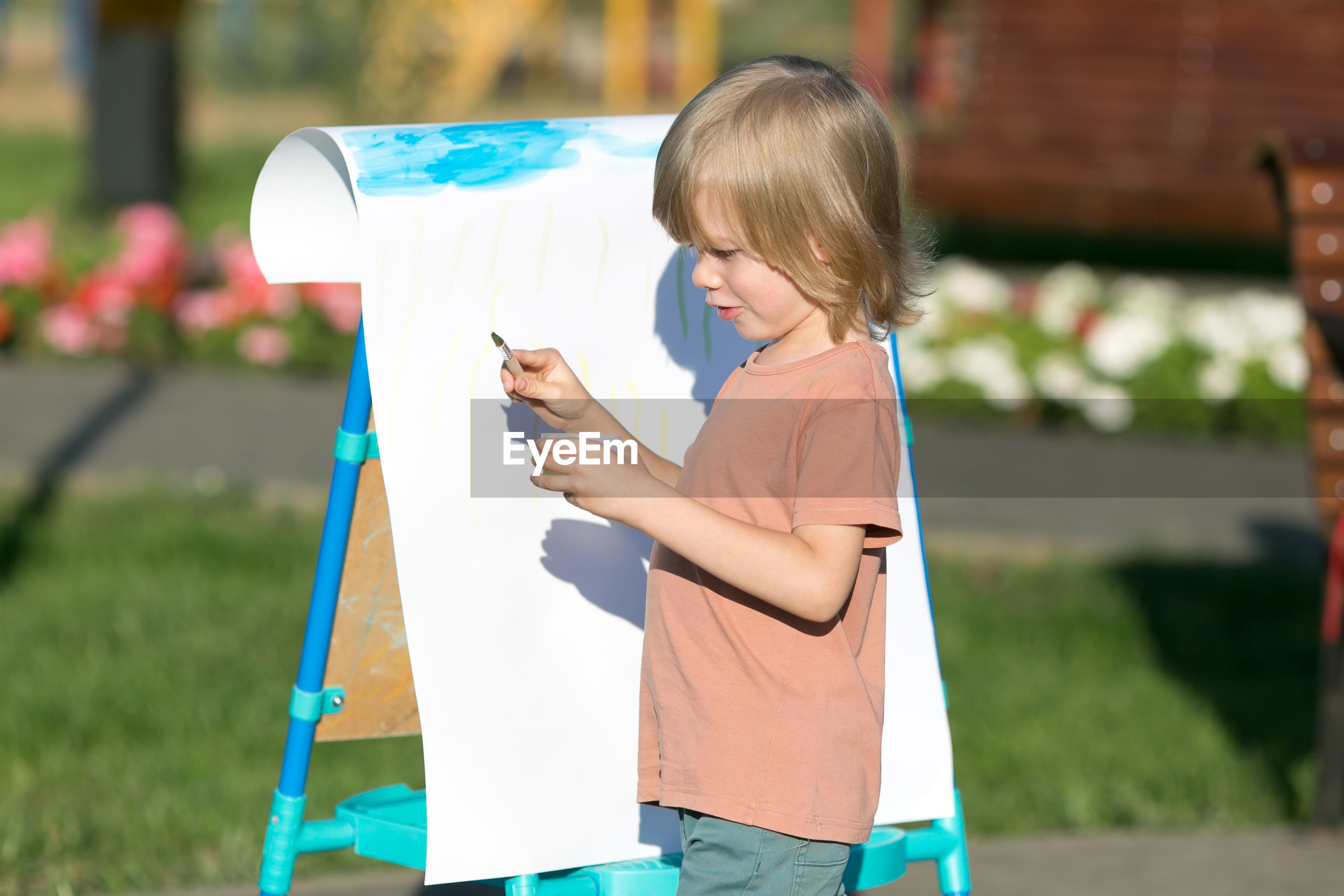 Side view of cute boy painting in park