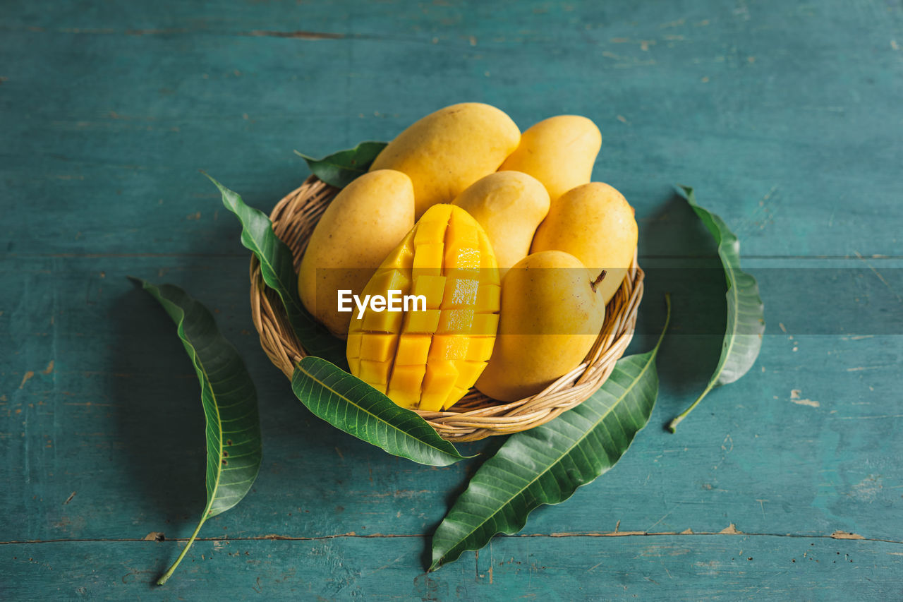 food, food and drink, freshness, healthy eating, wellbeing, table, leaf, plant part, fruit, still life, indoors, wood - material, yellow, basket, no people, directly above, citrus fruit, high angle view, orange color, green color, orange