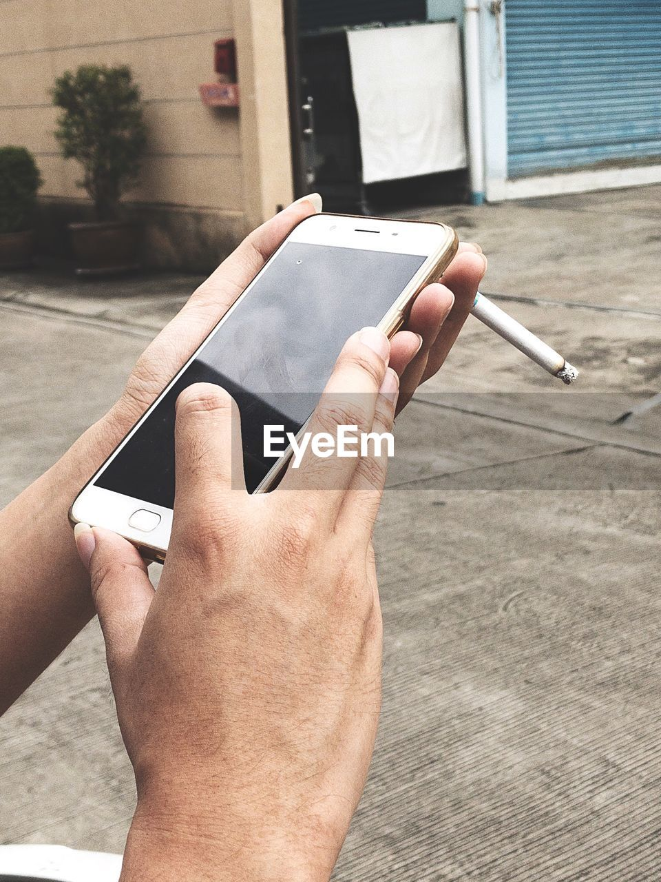 Close-up of man with cigarette using mobile phone