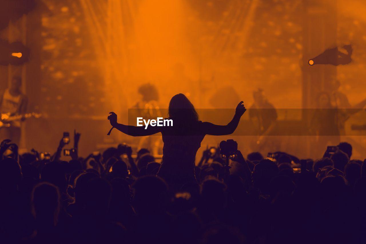 Silhouette of people enjoying music concert
