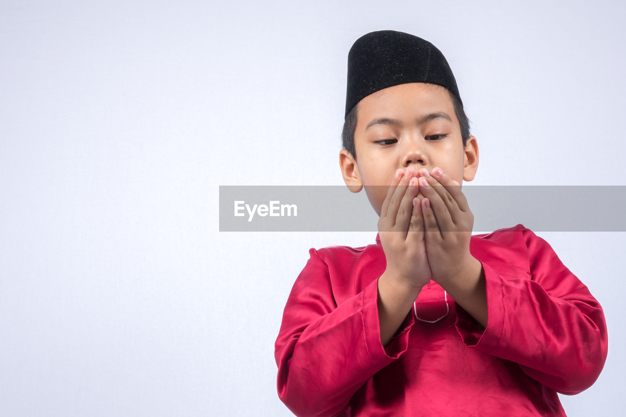 Cute boy wearing maroon traditional clothing standing against white background