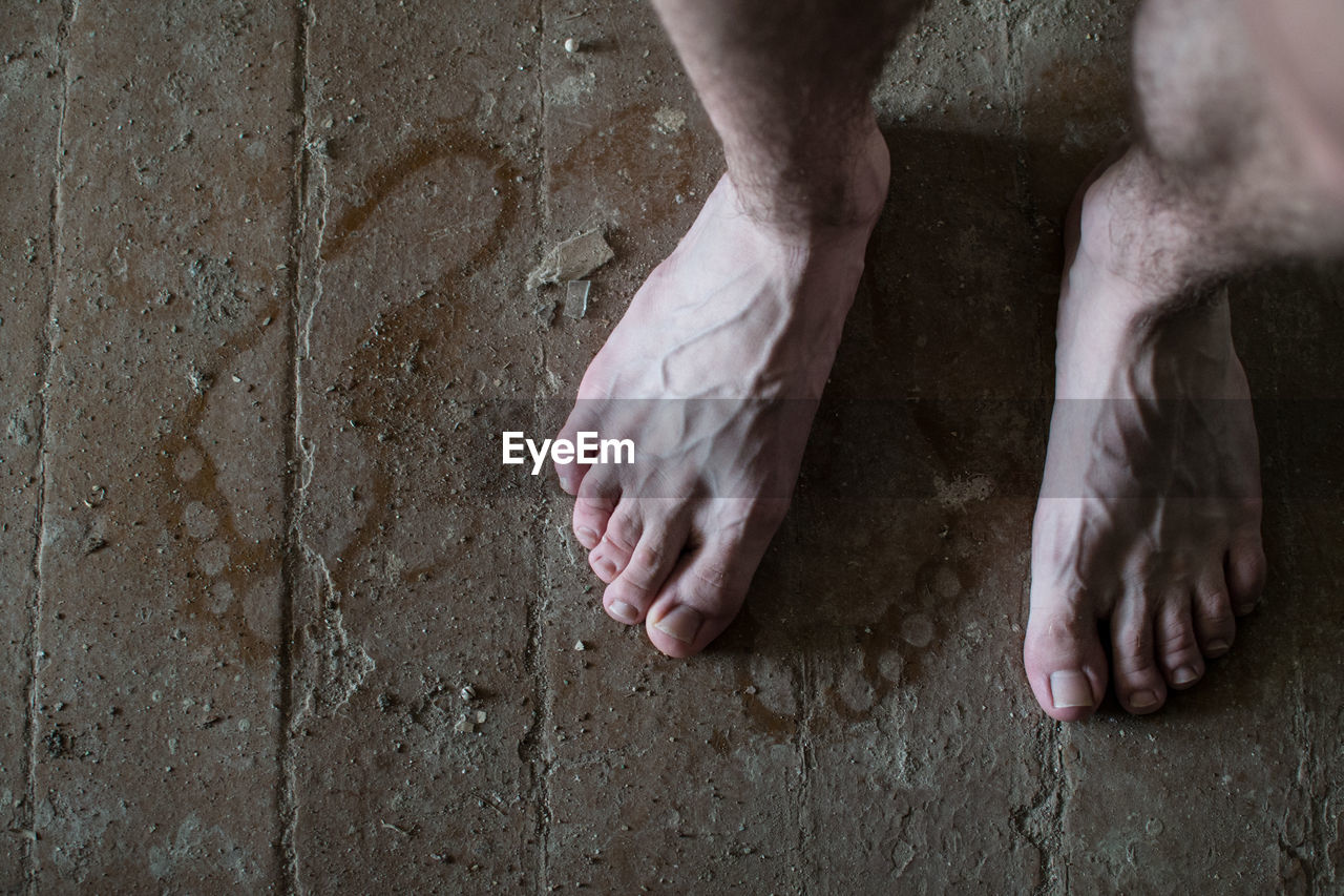 human body part, low section, one person, body part, human leg, real people, barefoot, human hand, hand, men, lifestyles, standing, wall - building feature, day, indoors, limb, human foot, human limb, high angle view, dirty