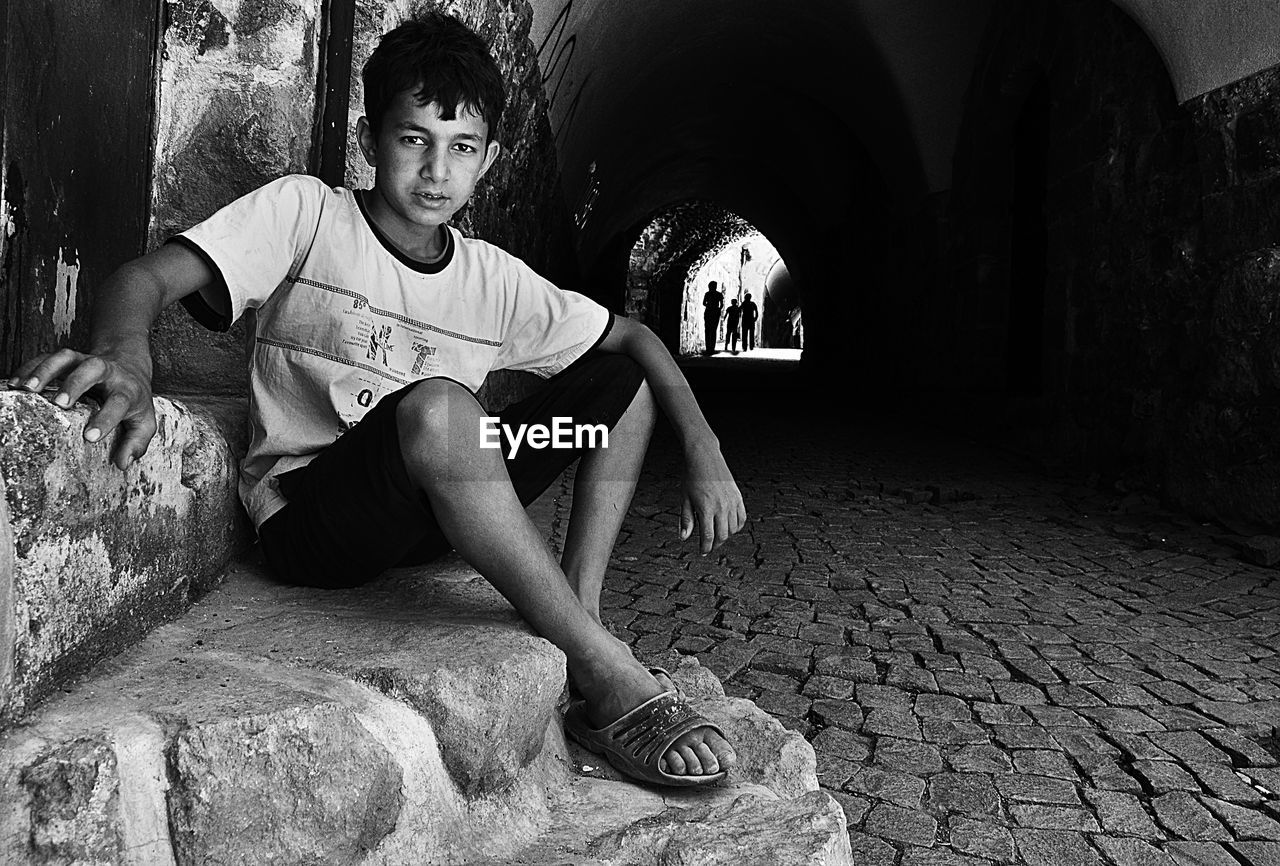 Portrait of cute boy sitting in cave