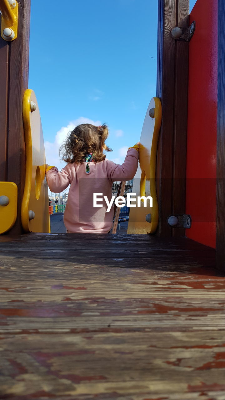 Rear view of girl on outdoor play equipment